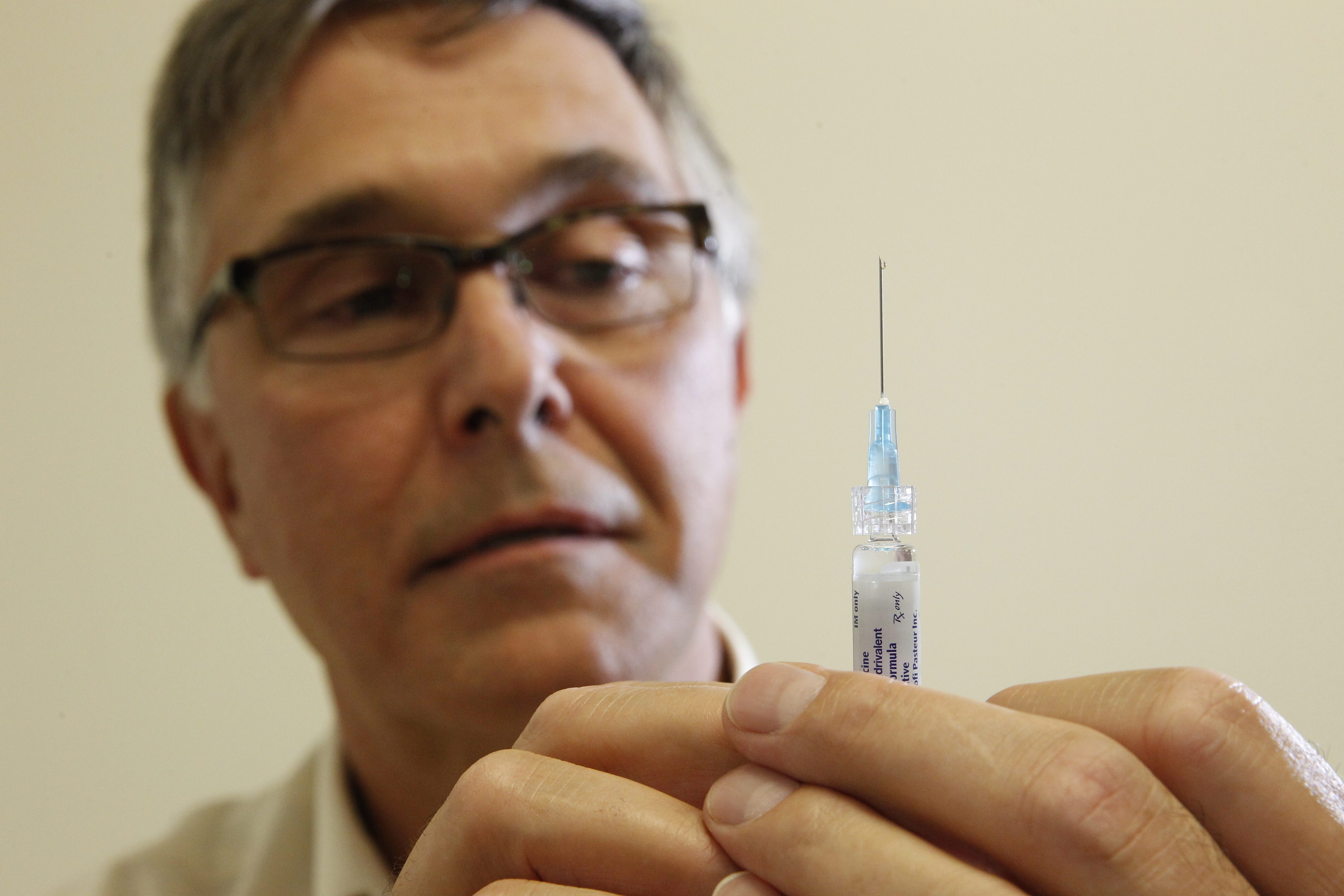 Pharmacist Matthew Buehler preps a flu vaccine before giving a staff member a shot Oct. 3 at Lifetime Health's Mosher Health Center Pharmacy on Main Street in Buffalo.