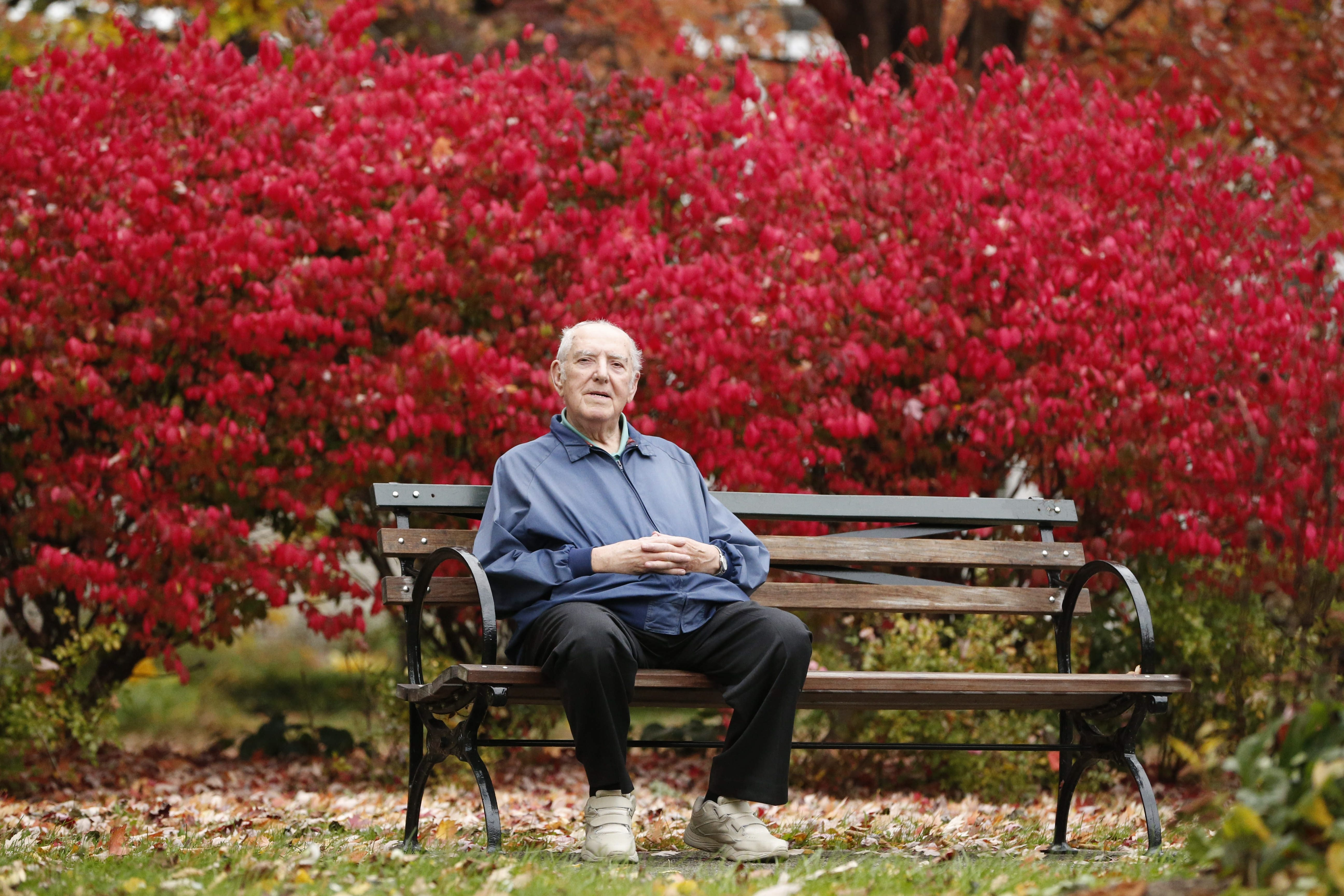Chris Marinaccio enjoys the warm temperatures and colorful fall scenery from a bench in front of blazing red foliage in Buffalo's Symphony Circle on Tuesday.