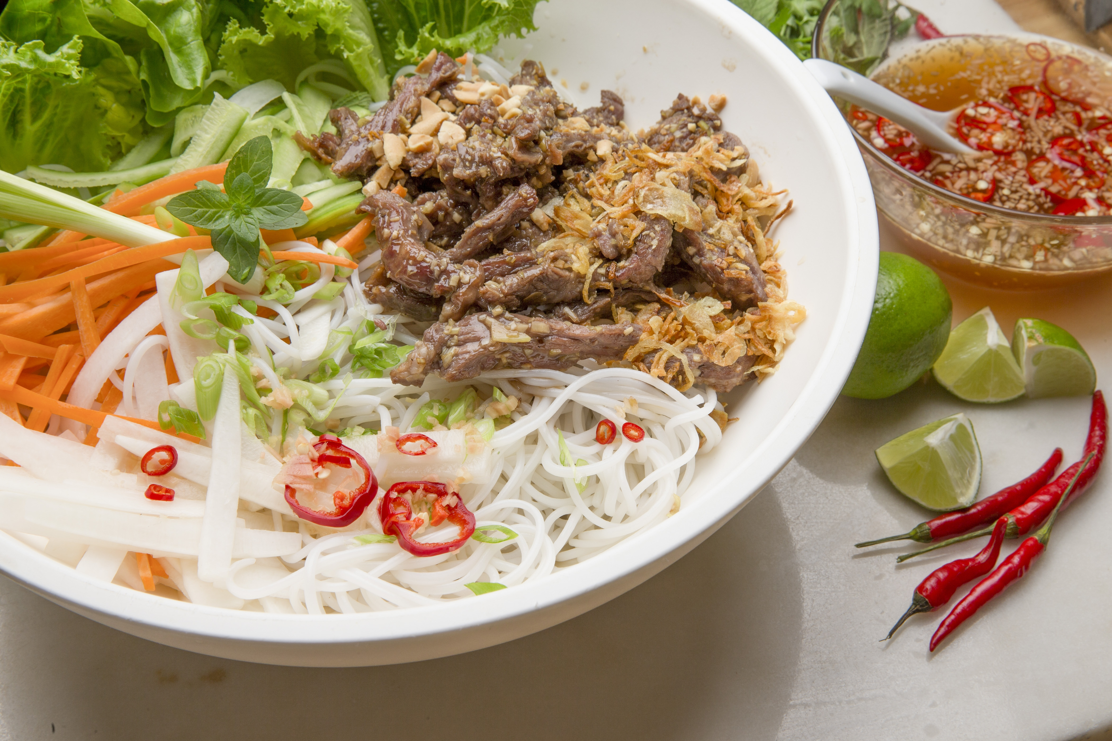 A bowl of bun bo xao, a warm is a made-to-order Vietnamese noodle salad made with beef, vegetables, crushed roasted peanuts and nuoc cham, a traditional fish  sauce.