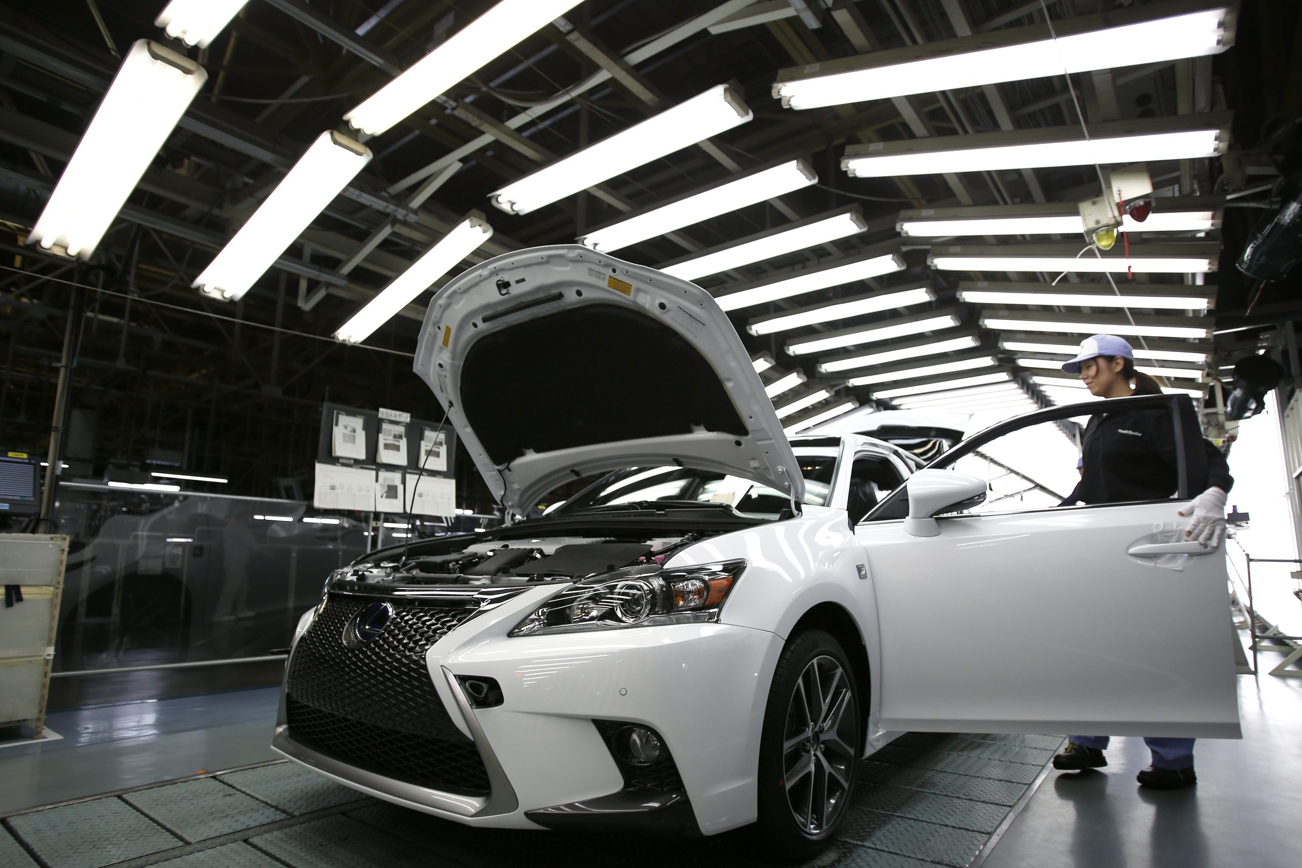 An employee inspects a Toyota Lexus CT200h F Sport vehicle on the production line at a Toyota plant in Miyawaka, Japan.