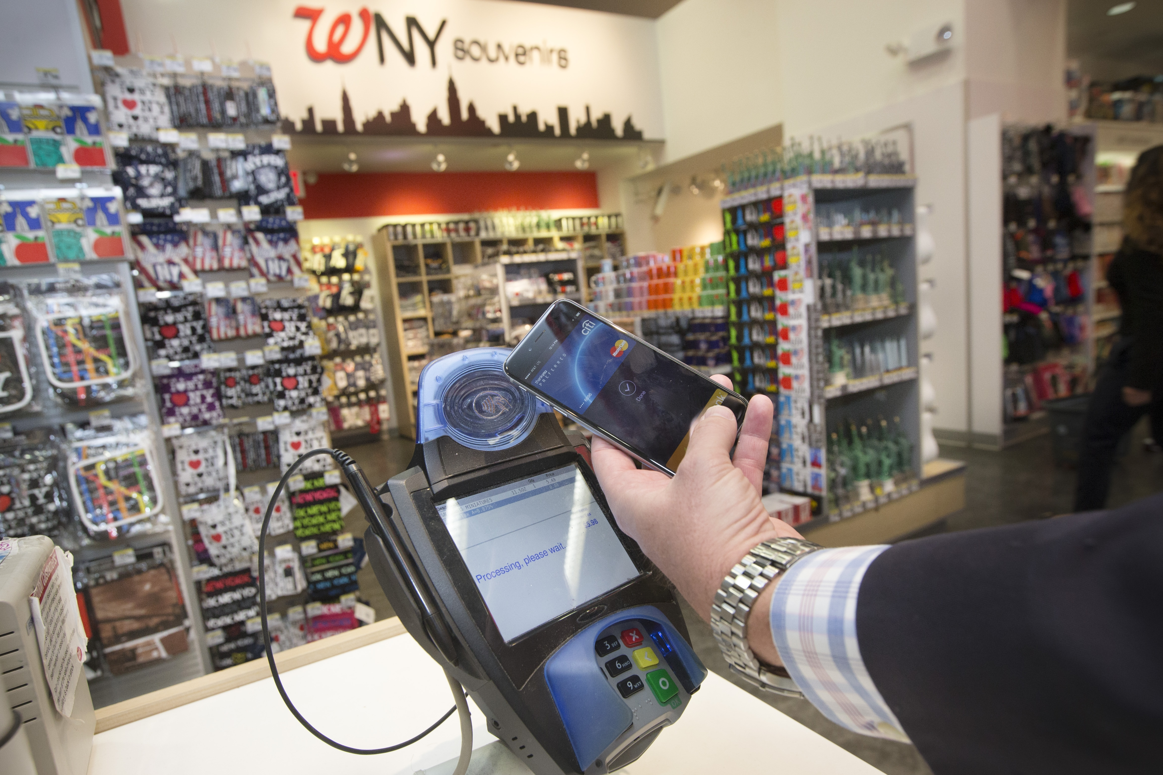 A customer makes a purchase with a MasterCard using Apple Pay on the iPhone 6 at a Walgreens in Times Square last Monday, the day the service launched.