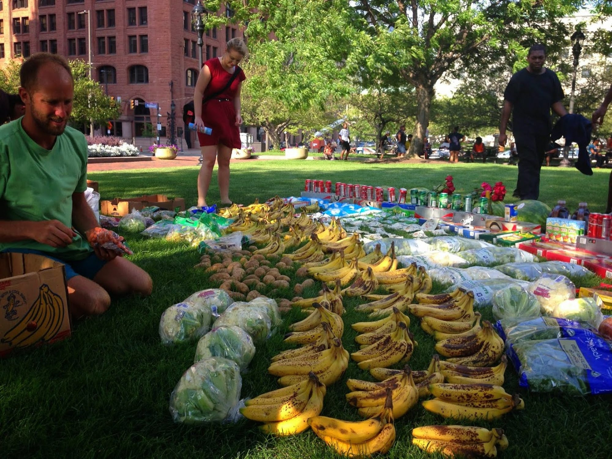 """All of the food laid out on the grass in Cleveland's Public Square was saved from dumpsters by Rob Greenfield, left, an environmental activist bicycling across the U.S., eating only food he finds in dumpsters. He creates """"food fiascoes"""" in many cities to showcase the food he's found."""