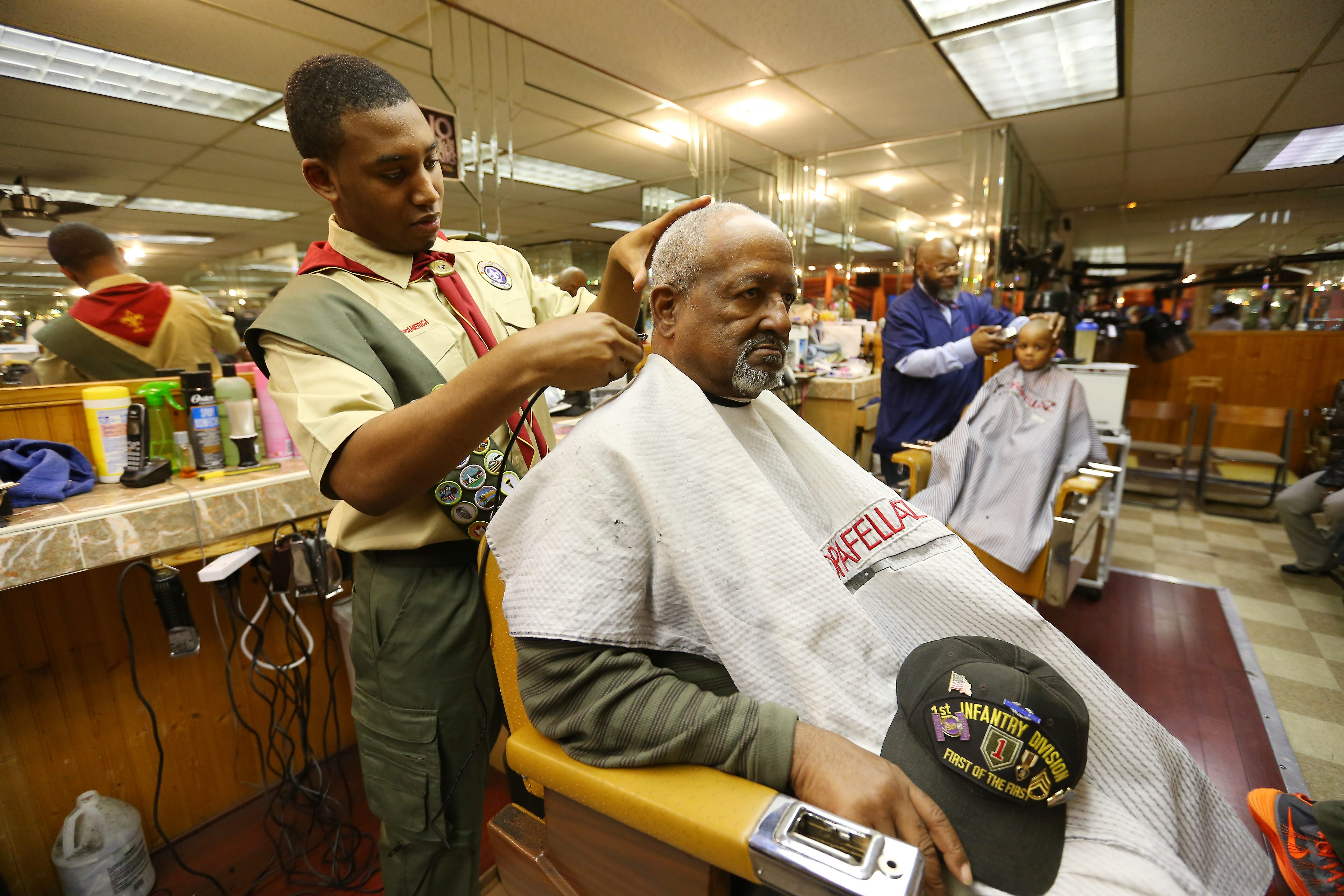 Eagle Scout candidate Justin Becton cuts the hair of Vietnam veteran and double Purple Heart recipient Hamilton A. Plummer at Chopafellaz in Buffalo on Tuesday. Justin, who works at the shop, organized haircuts for local veterans part of his Eagle Scout project.