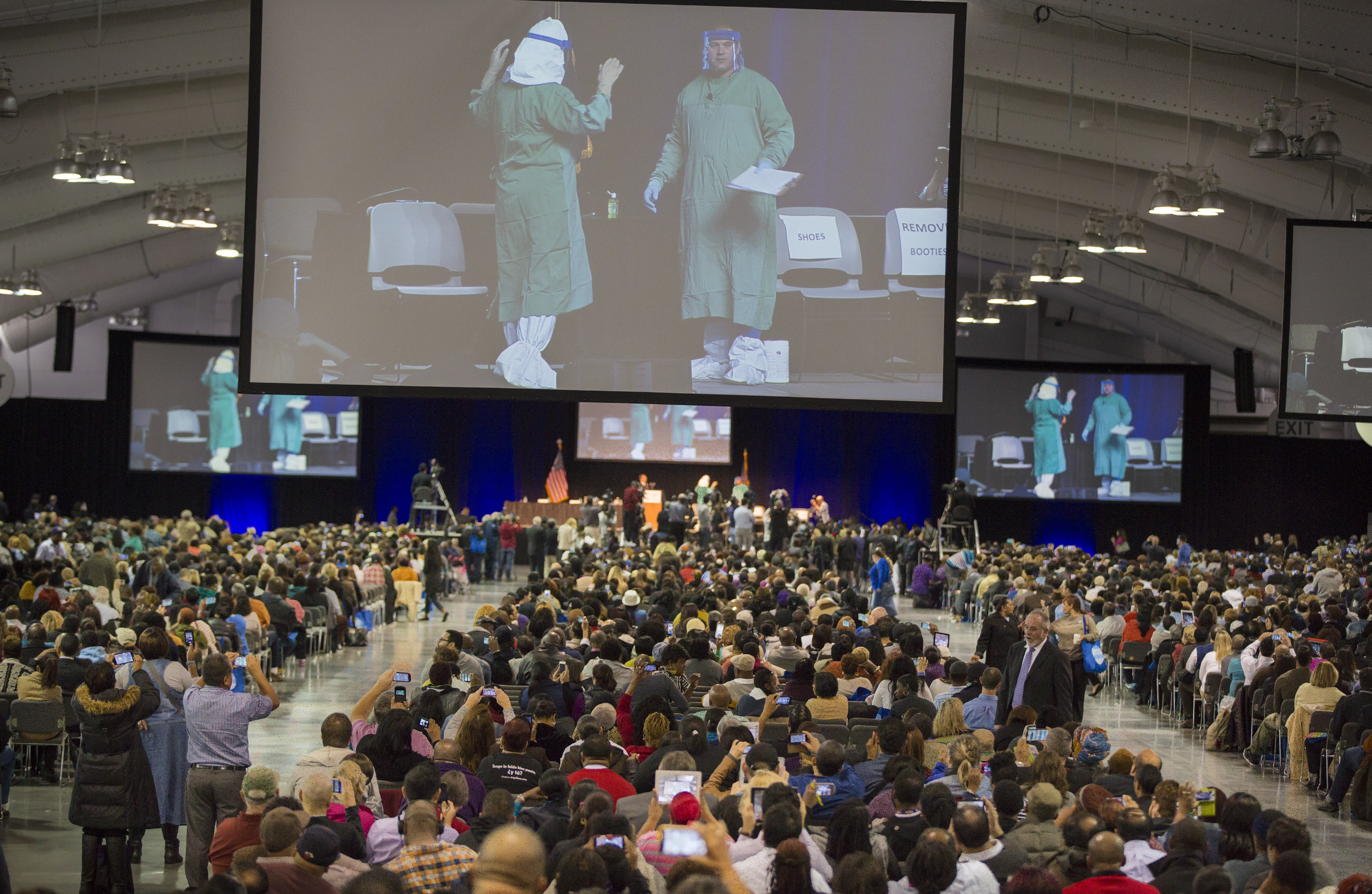 Officials on large screen demonstrate the proper way to don personal protective gear at an Ebola training session for thousands of health care workers in New York on Tuesday.