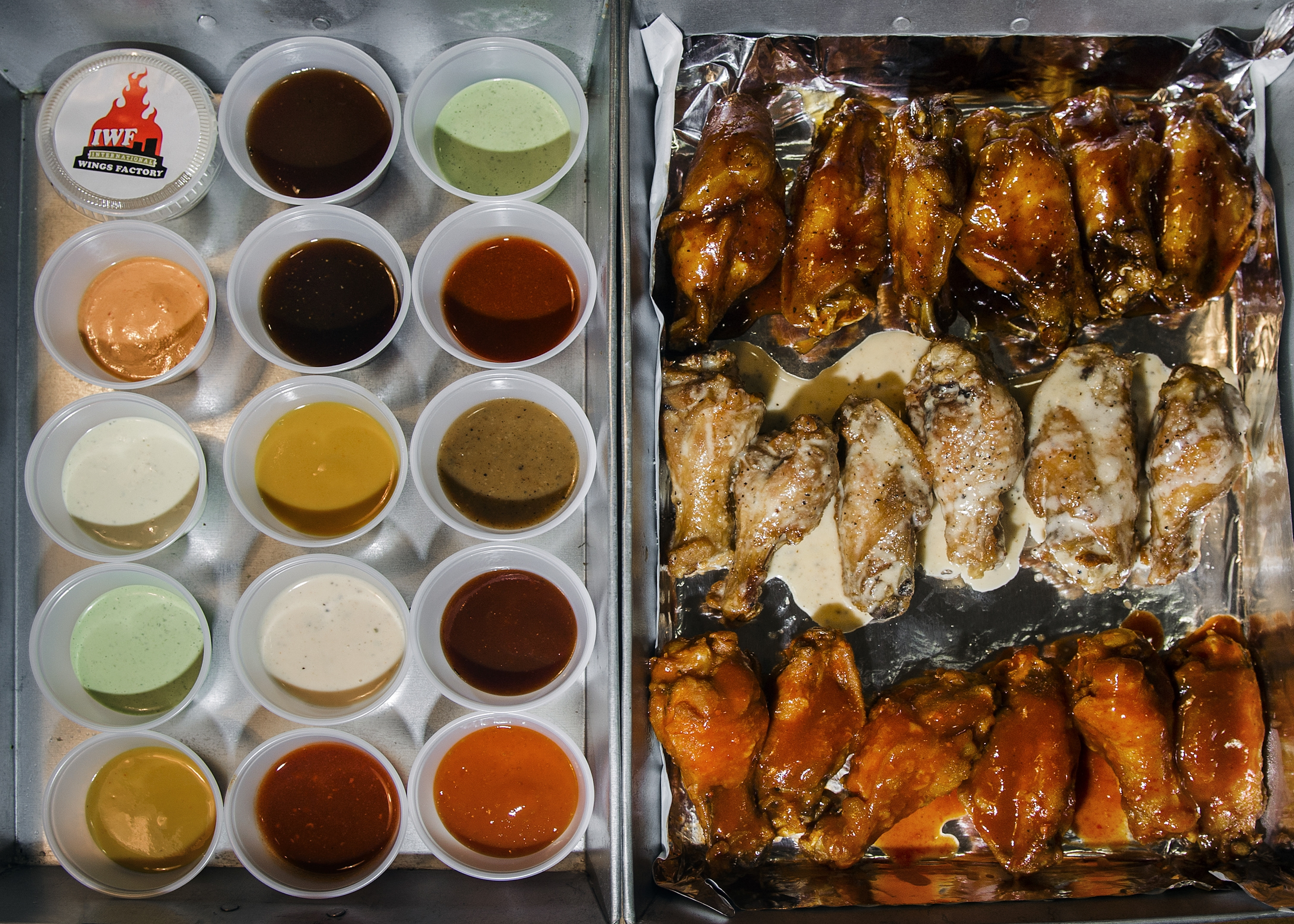 "A sampler from the International Wings Factory includes a variety of sauces and, from top, black pepper teriyaki, garlic Parmesan beurre blanc and ""soul purifier"" wings."
