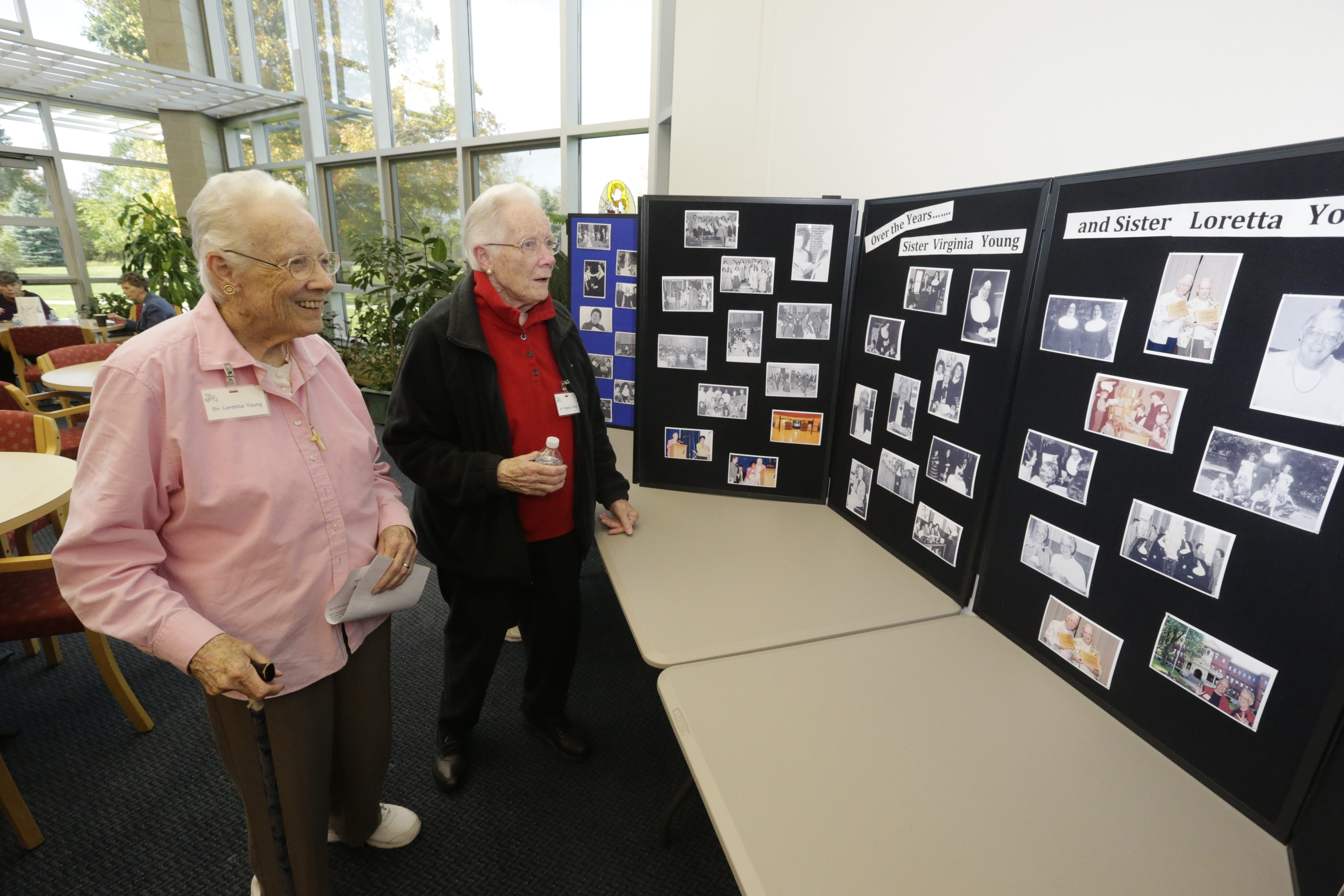 Sister Loretta Young, left, and her twin, Sister Virginia Young, look at old photographs during an open house to celebrate the 160th anniversary of the Sisters of St. Joseph in Buffalo on Sunday.