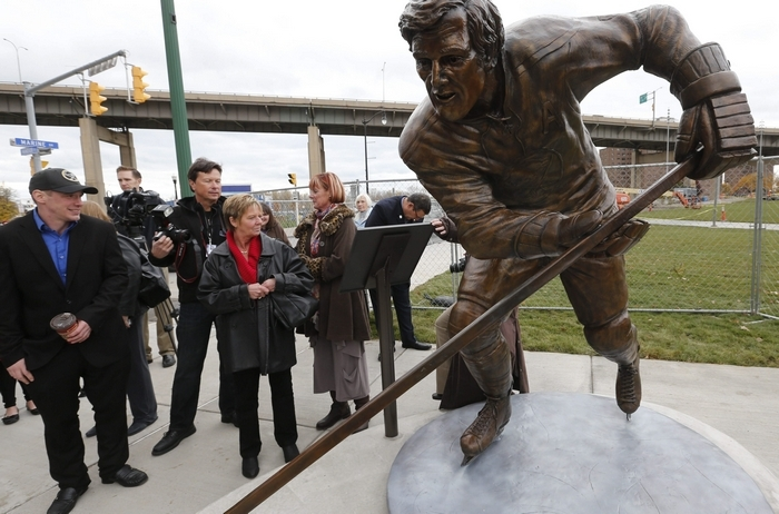 Visitors to the waterfront check out the statue of Tim Horton that was unveiled across the street from the new Tim Hortons Café & Bake Shop at HarborCenter on Thursday. (Derek Gee/Buffalo News)