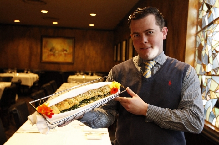 Nicolas Seveno, an assistant manager at Oliver's, presents the spinach loaf, a baguette with butter, spinach and herbs. (Sharon Cantillon/Buffalo News) (Sharon Cantillon/Buffalo News)