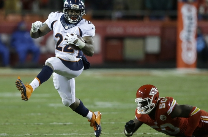 Broncos running back C.J. Anderson runs past Chiefs linebacker Justin Houston in Sunday night's game. Anderson ran for 168 yards. (Associated Press)