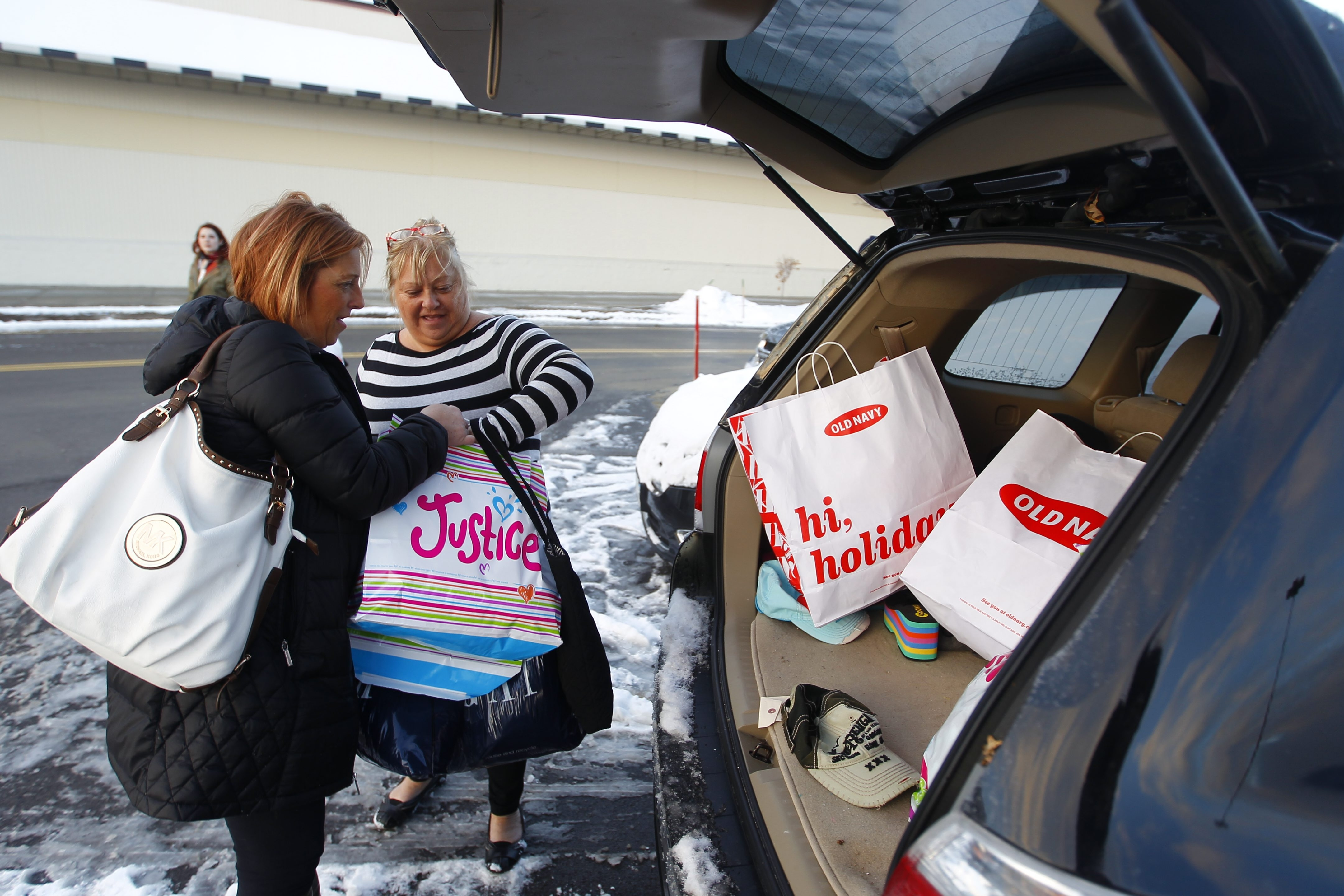Above left, Chris McKenzie and her daughter Brandi Alba load up the car after shopping on Black Friday  at the Walden Galleria. Above right,  Kim Paap, left, Marrianna Cantella and Joan Sullivan shop at the Fashion Outlet Mall in Niagara Falls on Friday. Below,  Vasily Ovsyannikov and Andrew Ned take their bargains to the car at Cabela's in Cheektowaga on Black Friday.
