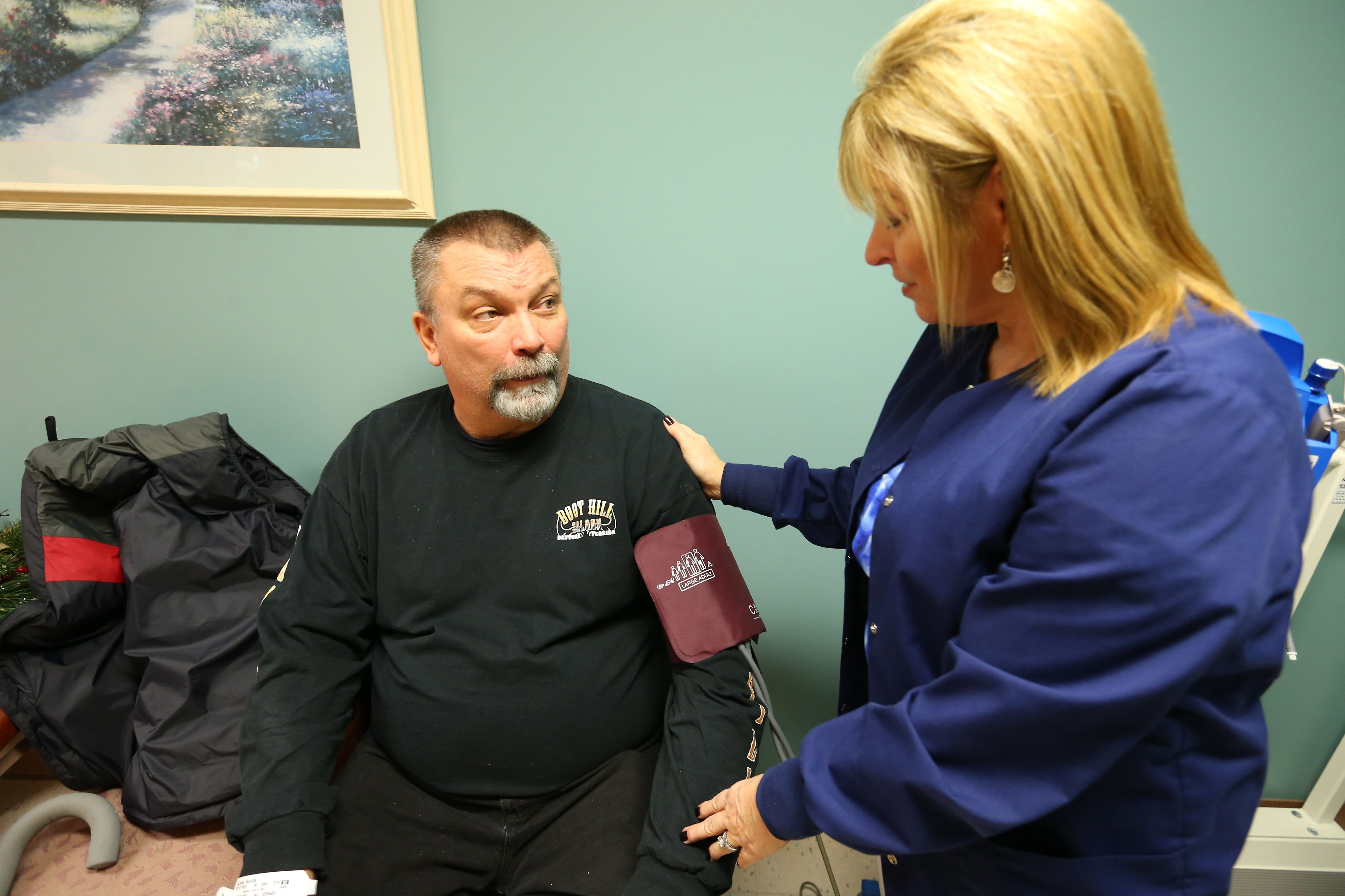 Melvin Bluhm has his blood pressure checked by Marsha Cleland, a registered nurse at Kenmore Mercy Hospital.