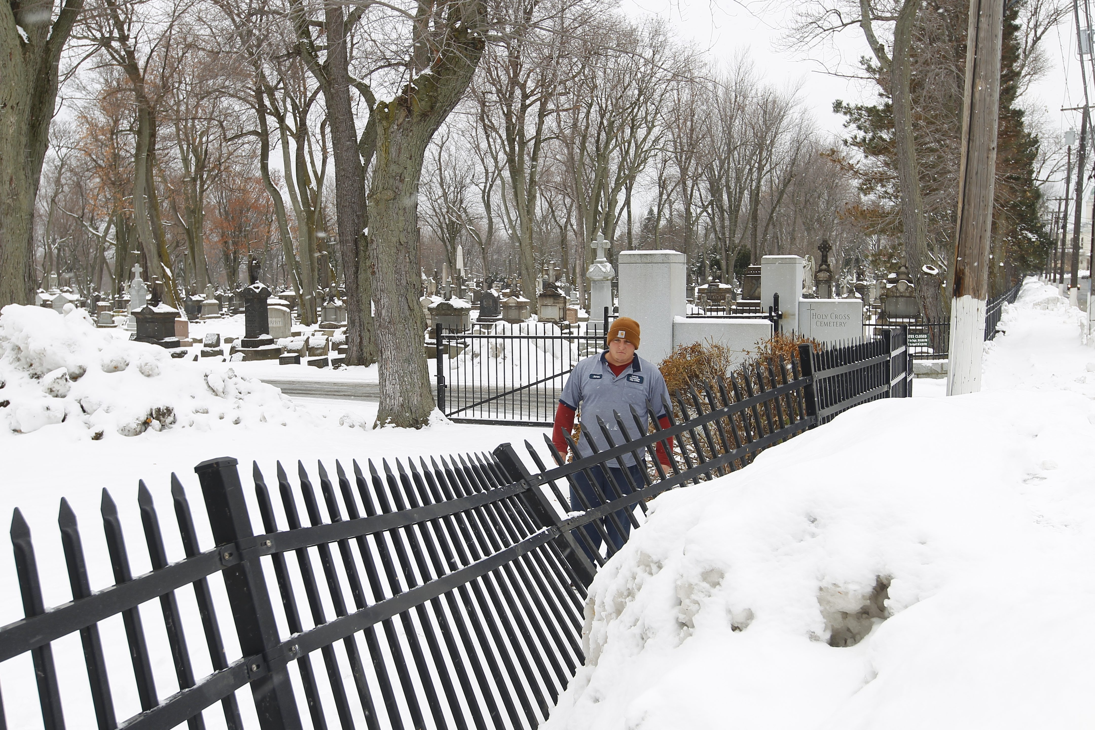Jim Roche, a groundskeeper at Holy Cross cemetery, looks at damage to a fence running along Ridge Road in Lackawanna. The Snowvember storm prevented employees from getting to work and delayed dozens of burials, which resumed Monday.