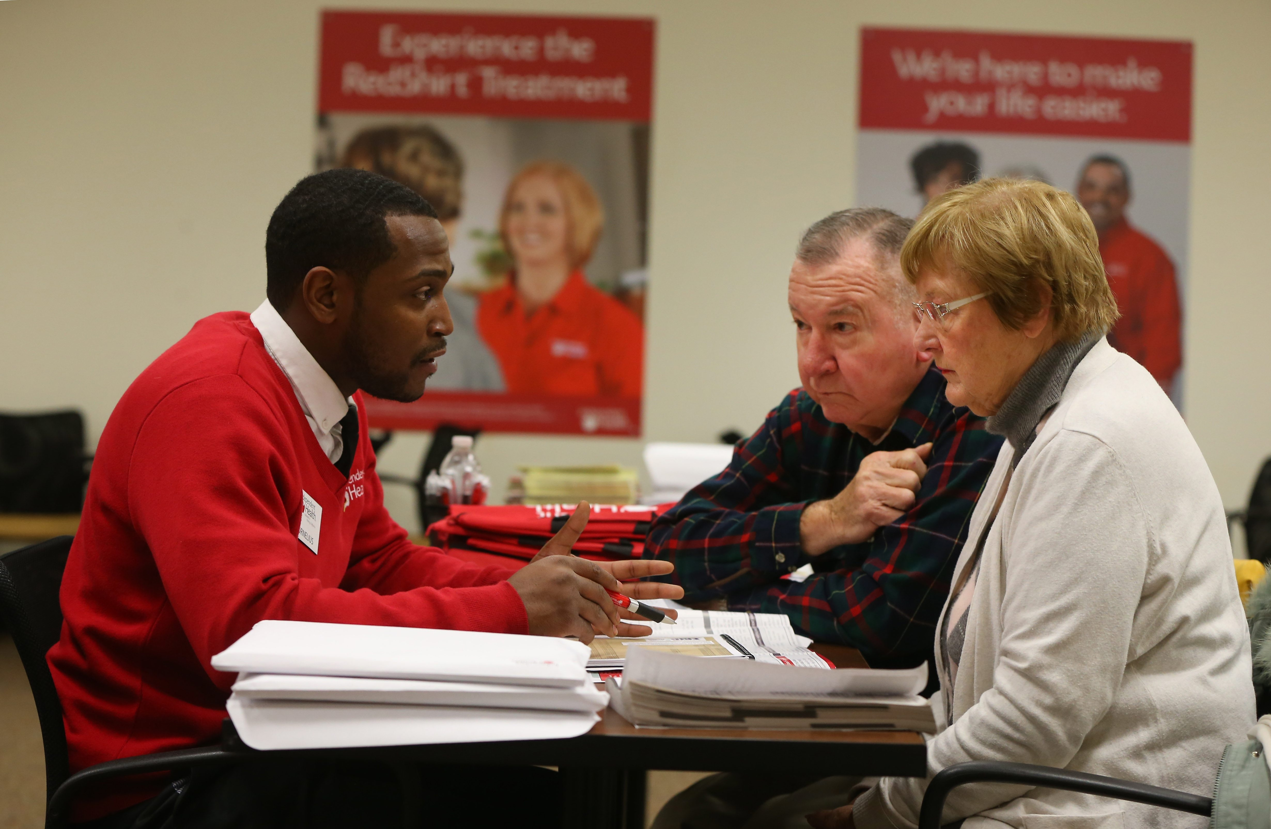 Independent Health's Cornelius DeLaney explains health insurance options to Stephen and Marlene Kotlowski at the Independent Health office in Depew on Friday.