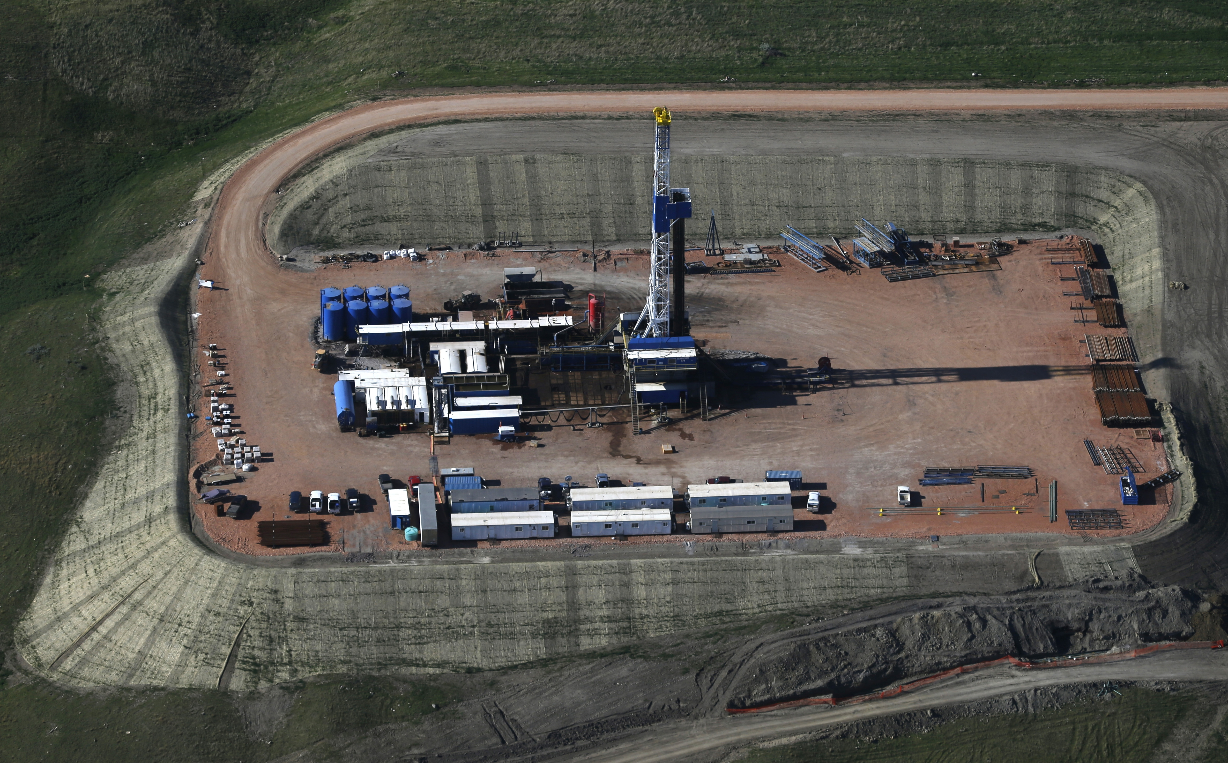 FILE - In this June 12, 2014, aerial photo, an oil well is drilled near Williston, N.D. A decision by OPEC not to cut oil production is hammering major energy companies in the U.S. and abroad. Chevron, ConocoPhillips and Exxon Mobil are down more than 4 percent. Britainís BP is down 6 percent. Natural gas producers are getting hit as well. Chesapeake Energy is down almost 12 percent. Benchmark U.S. crude prices plunged almost 7 percent $68.81 early Friday, Nov. 28. (AP Photo/Charles Rex Arbogast, File)