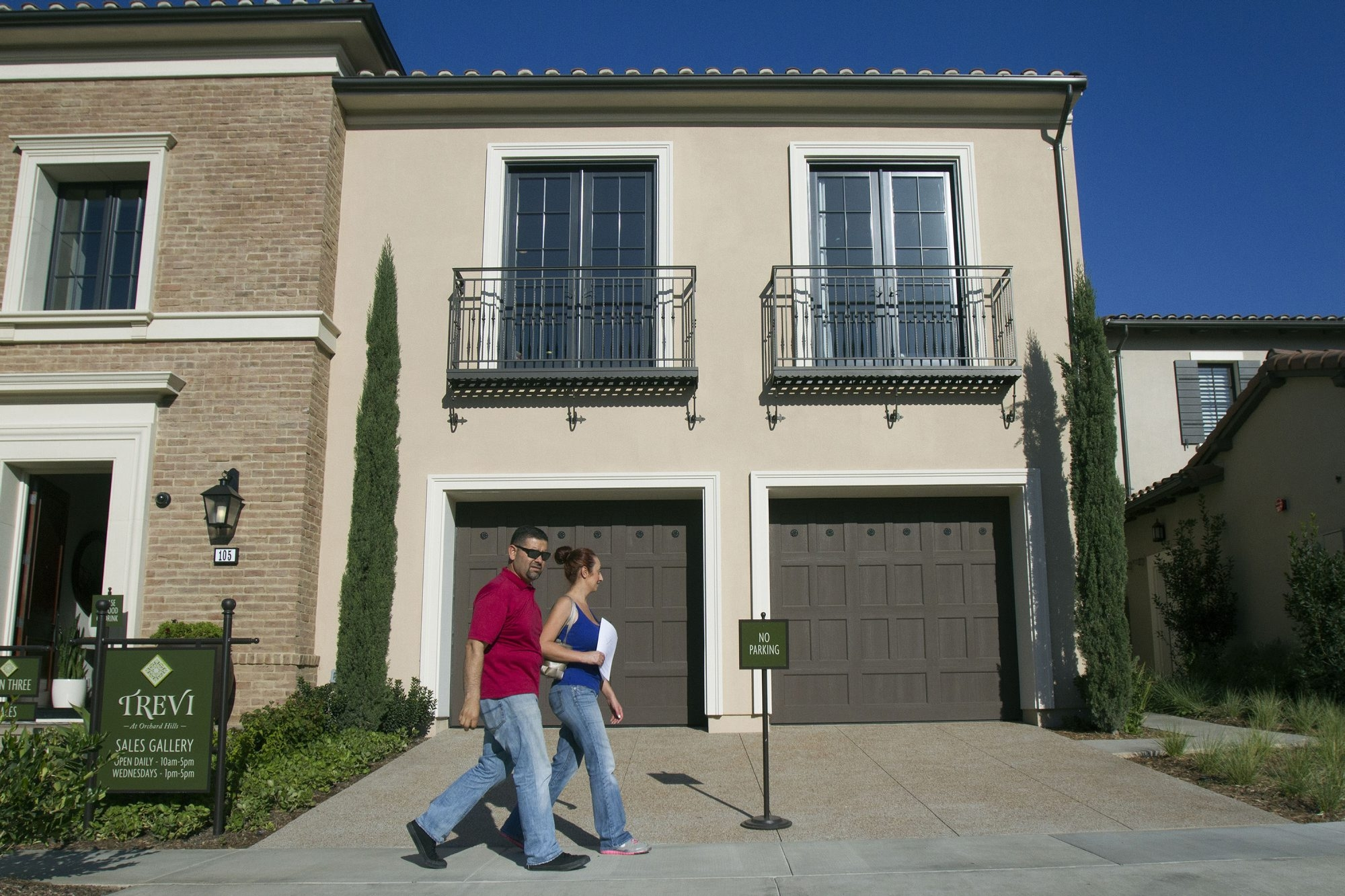 Rafael Lopez, left, and his wife, Jacqueline, step out of a model home at Trevi and Amelia luxury homes on Nov. 21, 2014 in the Orchard Hills community in Irvine, Calif. The housing market has recently been a little sluggish with flat prices and sales numbers decreasing. However, it has been different for the rich, who have been buying more luxury home sales in Southern California. (Cheryl A. Guerrero/ Los Angeles Times/TNS)