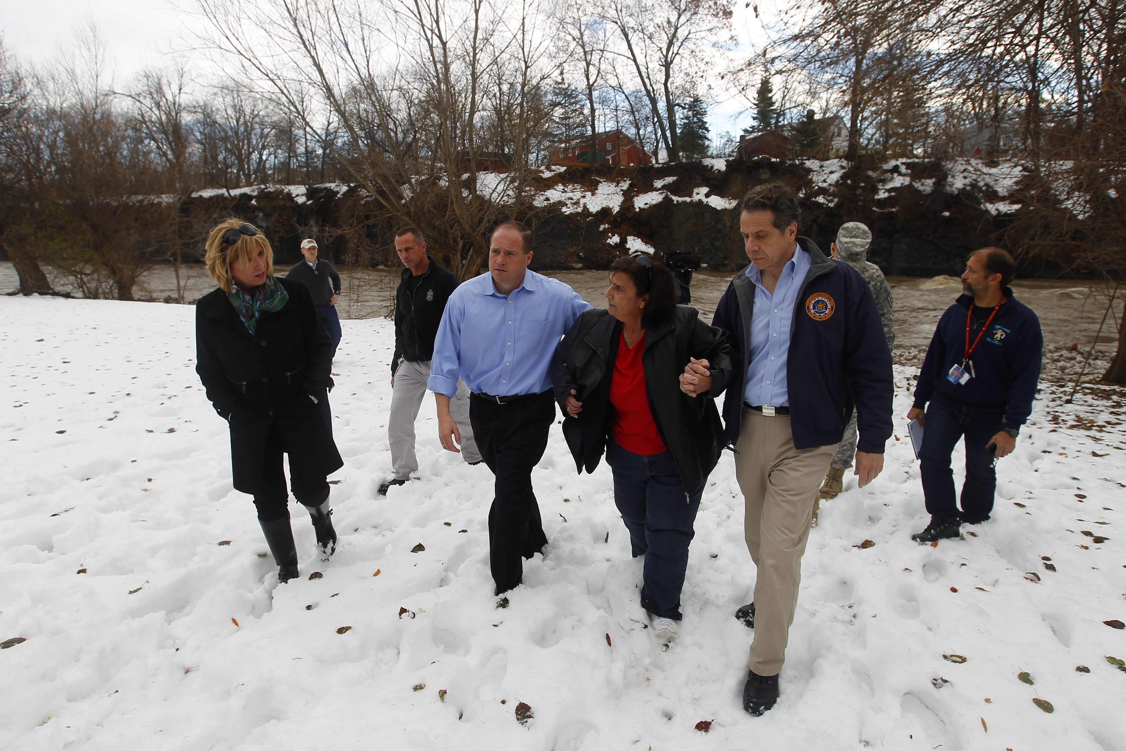 State Sen. Timothy M. Kennedy, center left, and Gov. Andrew M. Cuomo walk with West Seneca resident Nancy S. Barletta after taking a look at water from Cazenovia Creek run- ning through her Willowdale Drive backyard amid continuing concerns about flooding.