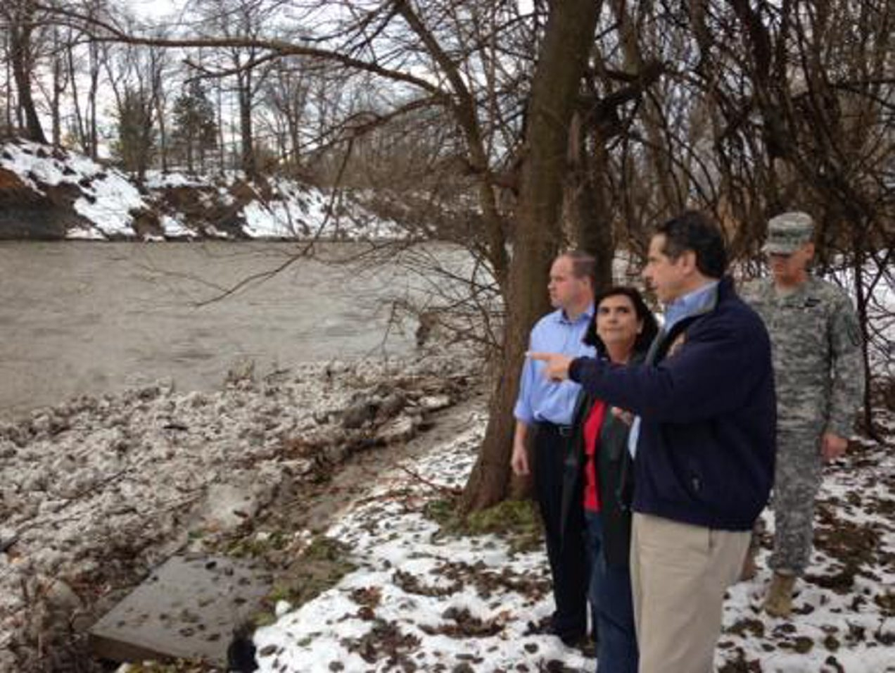 Gov Andrew Cuomo looks at rising waters of Cazenovia Creek on Willowdale Drive in West Seneca today. (John Hickey/Buffalo News)