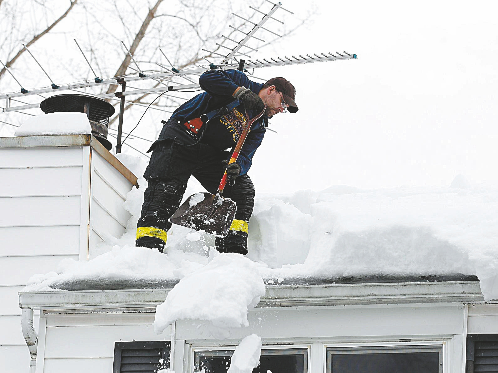 The East Seneca Fire Company responded to the home of one of their elderly members to remove snow from his roof, Sunday, Nov. 23, 2014.  65 year member of the department, Jim Brady, 85, heard creaking at his home on Leydecker Road  and a small section of his barn had already collapsed, so he called the fire station. (Sharon Cantillon/Buffalo News)