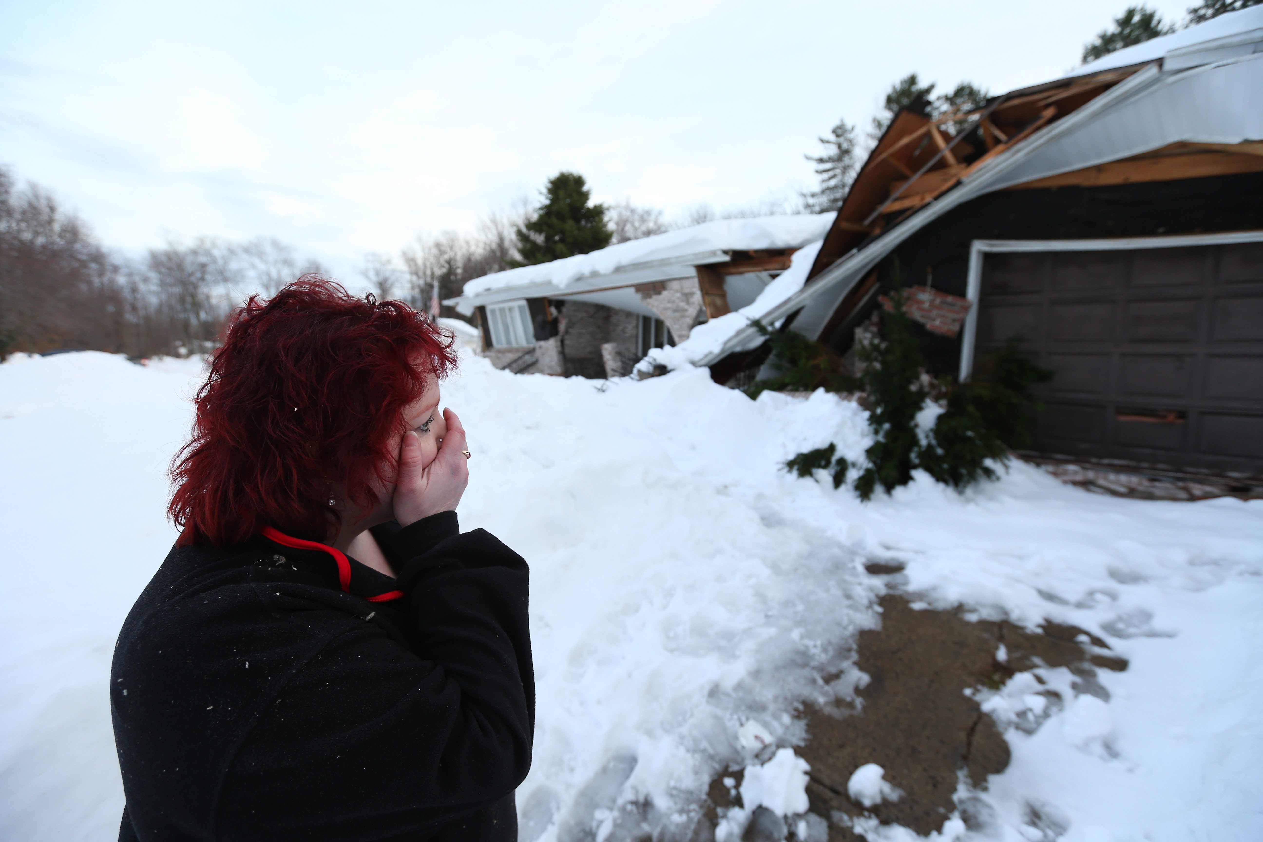 Tami Diestler is distraught as she checks damage to the Alden home she and husband Michael escaped early Thursday when snow caused a cave-in.