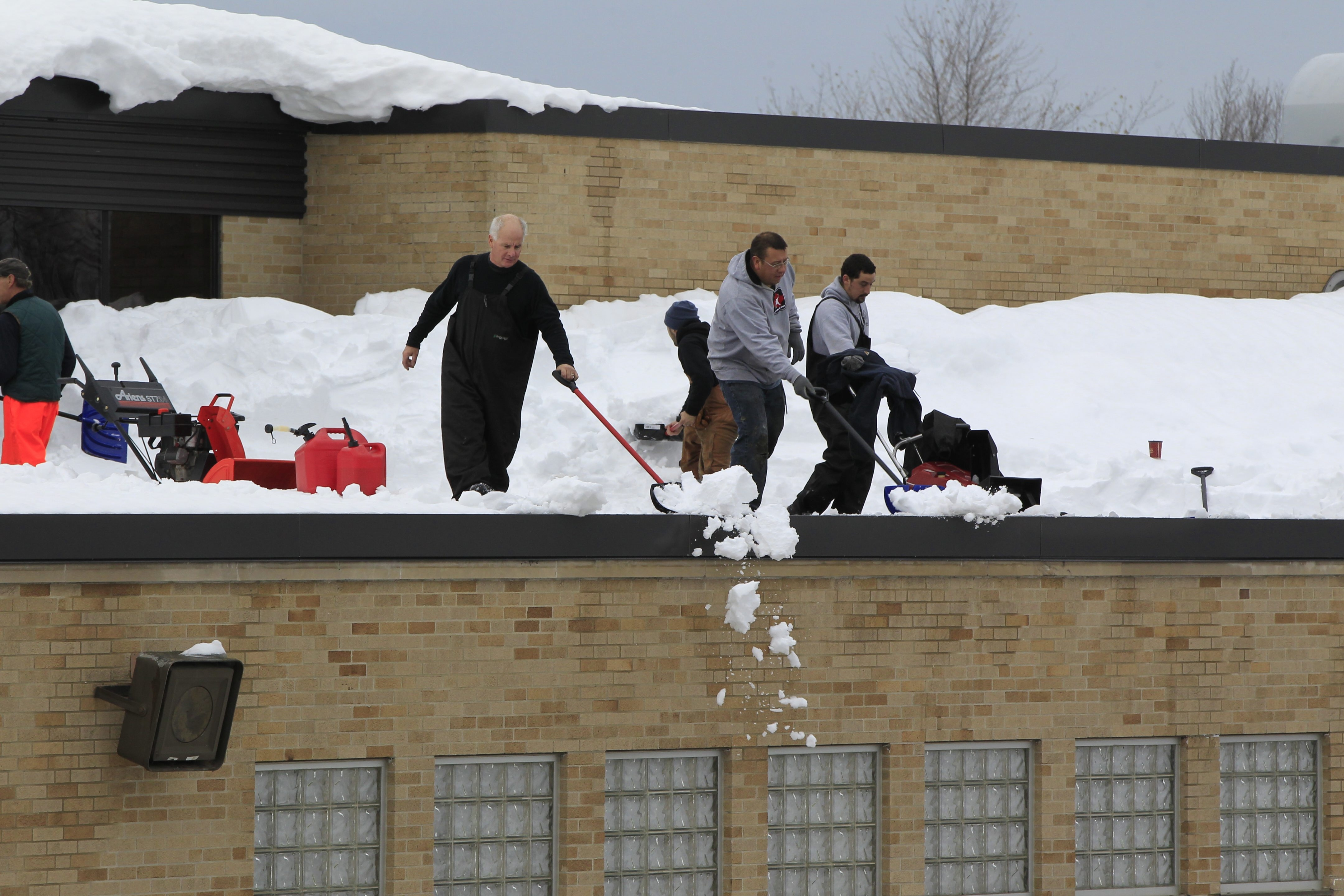 Workers use shovels and snowblowers to clear the roof of Hamburg High School on Sunday. The district is one of several in the area that will not reopen until Dec. 1, after the Thanksgiving holiday. Districts are also rearranging their calendars to make up for lost time.