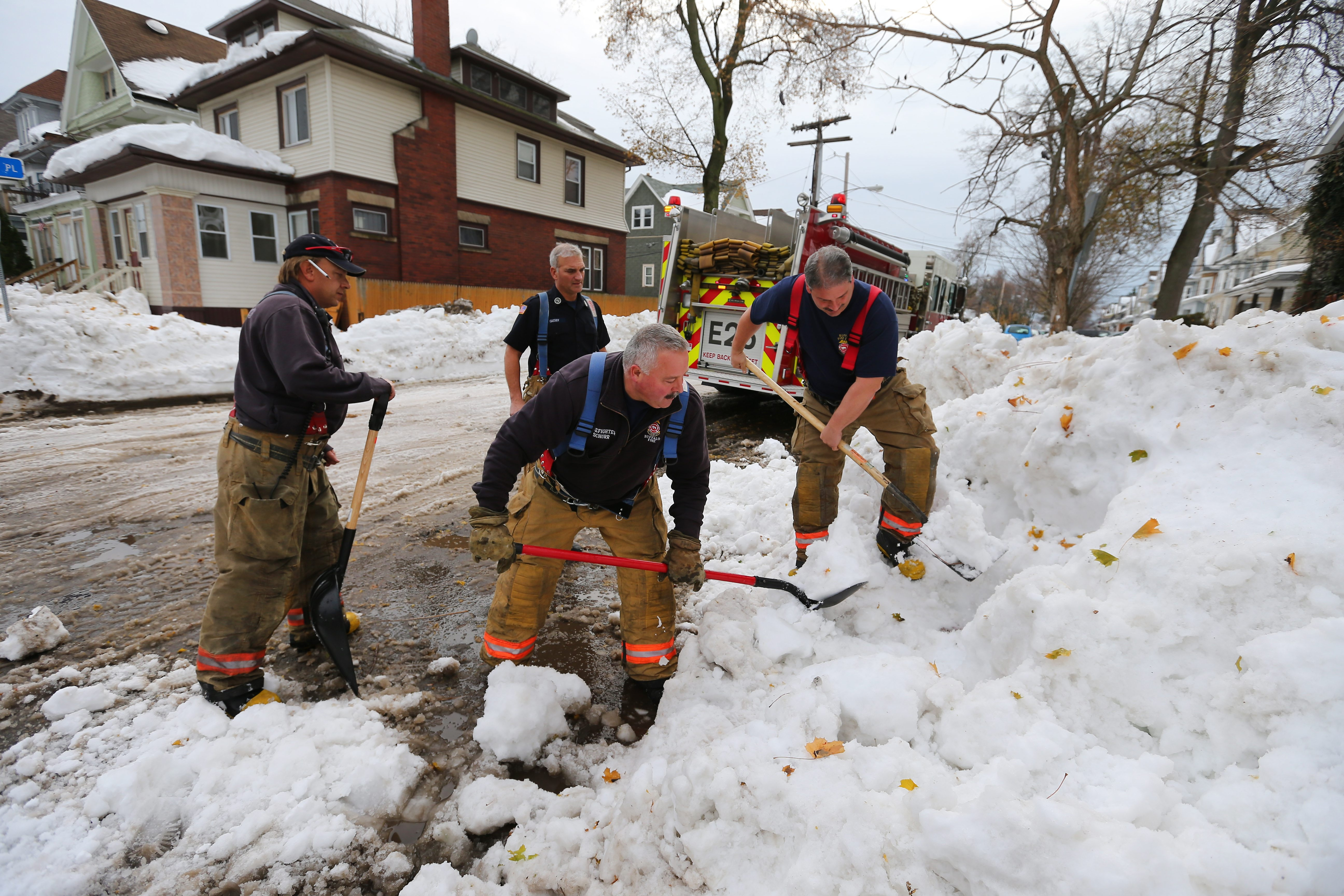 Buffalo firefighters from Engine 25 try to locate a fire hydrant on the corner of Paul Place and Seneca Street in South Buffalo on Nov. 23.