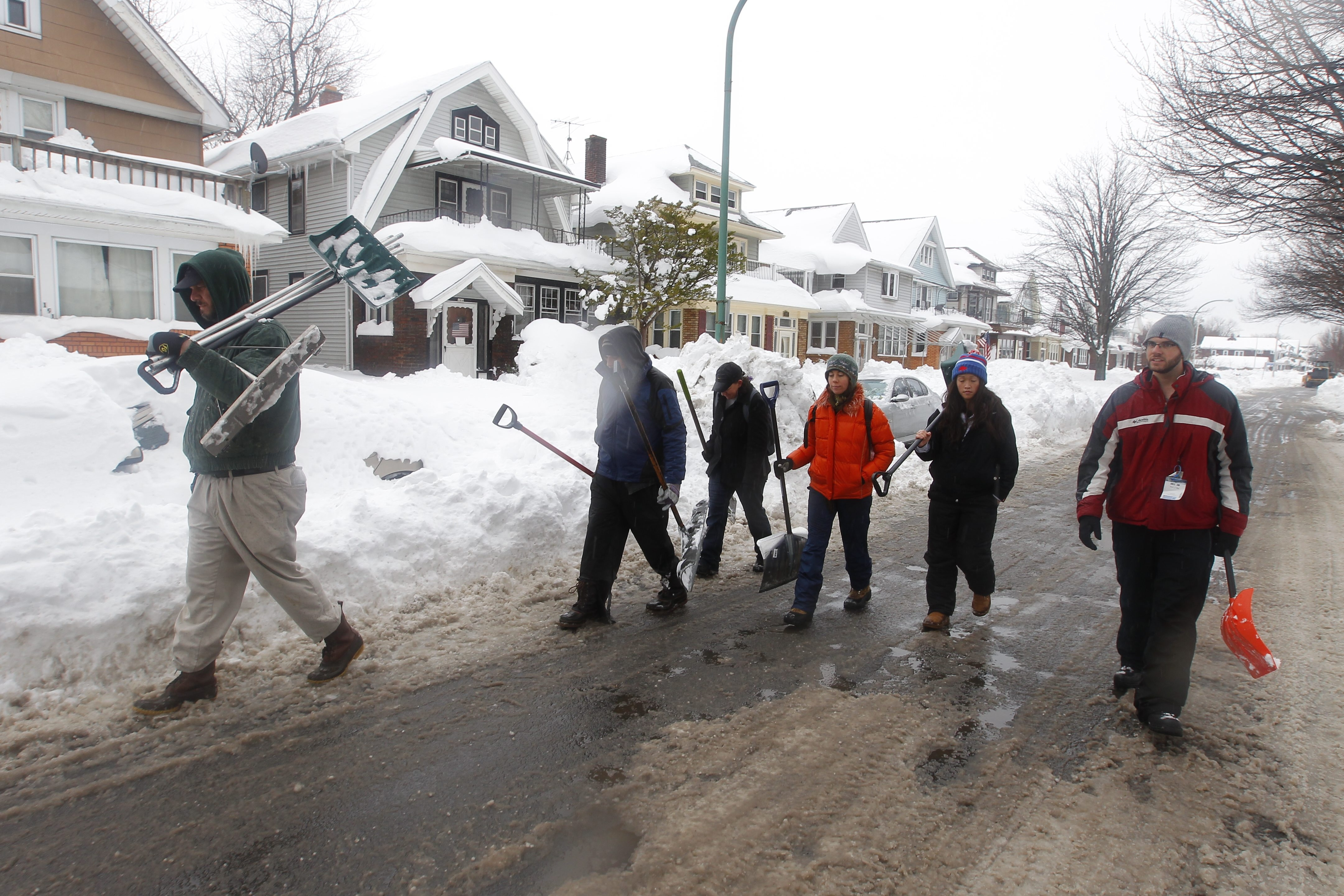Volunteer Shovel Brigade members march down Stephenson Street in South Buffalo on Saturday looking for homeowners who needed help.