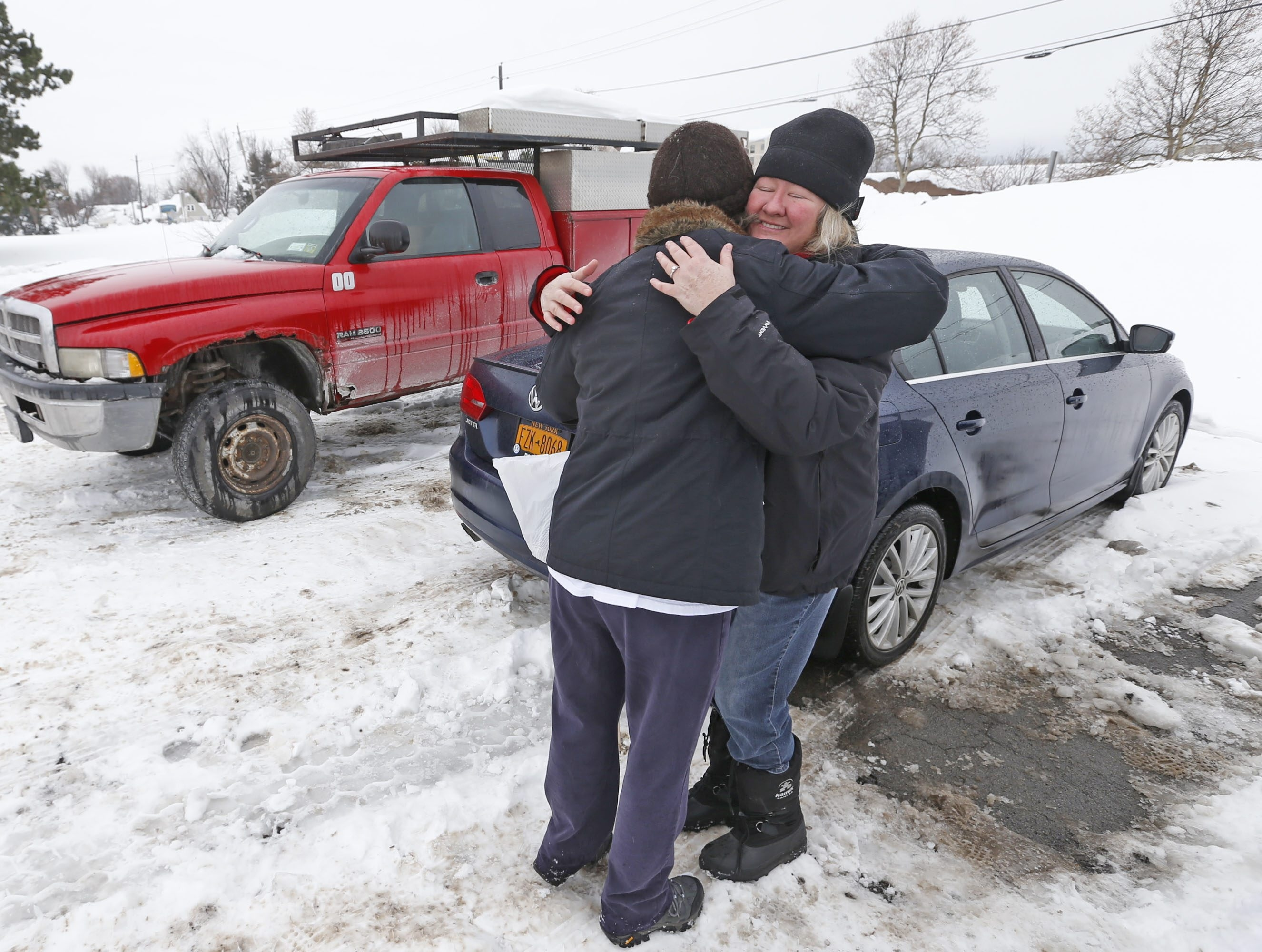 Kathy Schrecongast of East Aurora, left, hugs her sister-in-law Carol Alex in the old Seneca Mall parking lot Saturday, where they were retrieving Schrecongast's car.