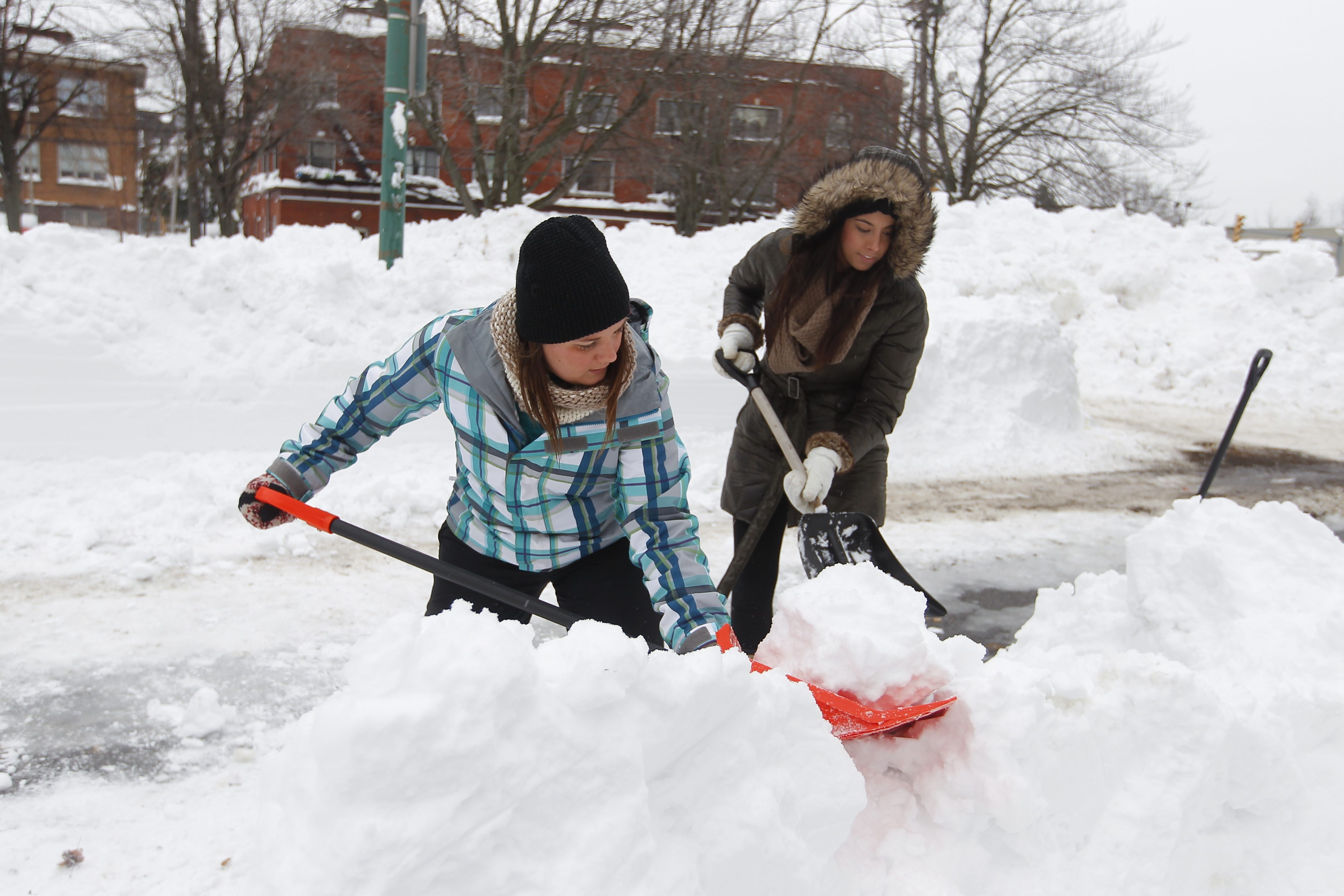Volunteer shovel brigade members Rachael Pellinger, left, and Megan Spiegelhoff  both of North Buffalo shovel snow  from a base of a driveway on Mineral Springs road  in Buffalo, N.Y. , on Saturday  November  22, 2014.This day 5 of Lake effect storm that barreled into WNY .(John Hickey/Buffalo News)