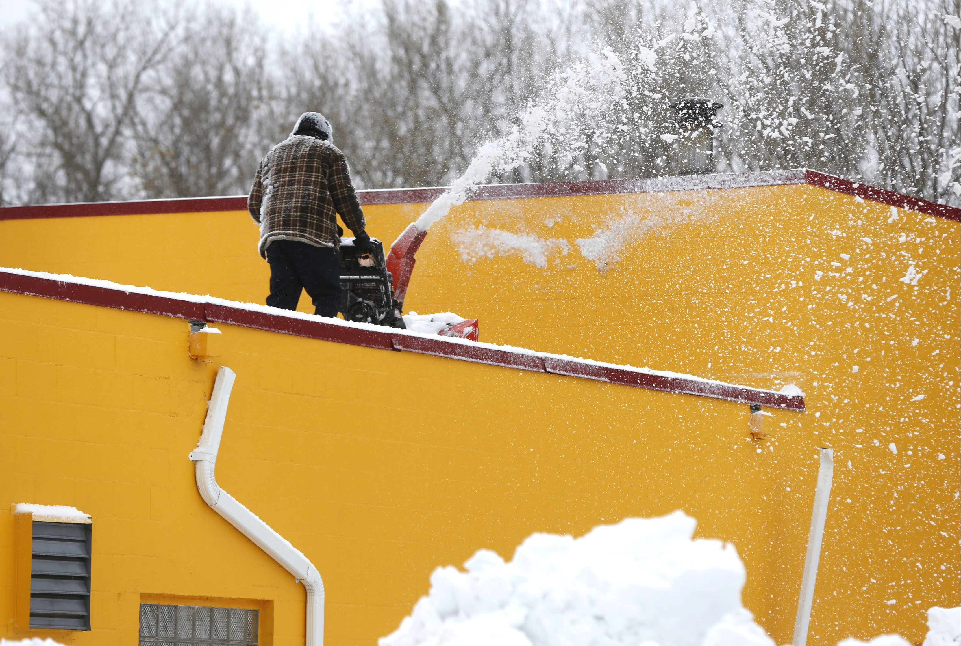 A man uses a snow blower on the roof of Continental Transmission on Orchard Park Road in West Seneca on  Saturday.