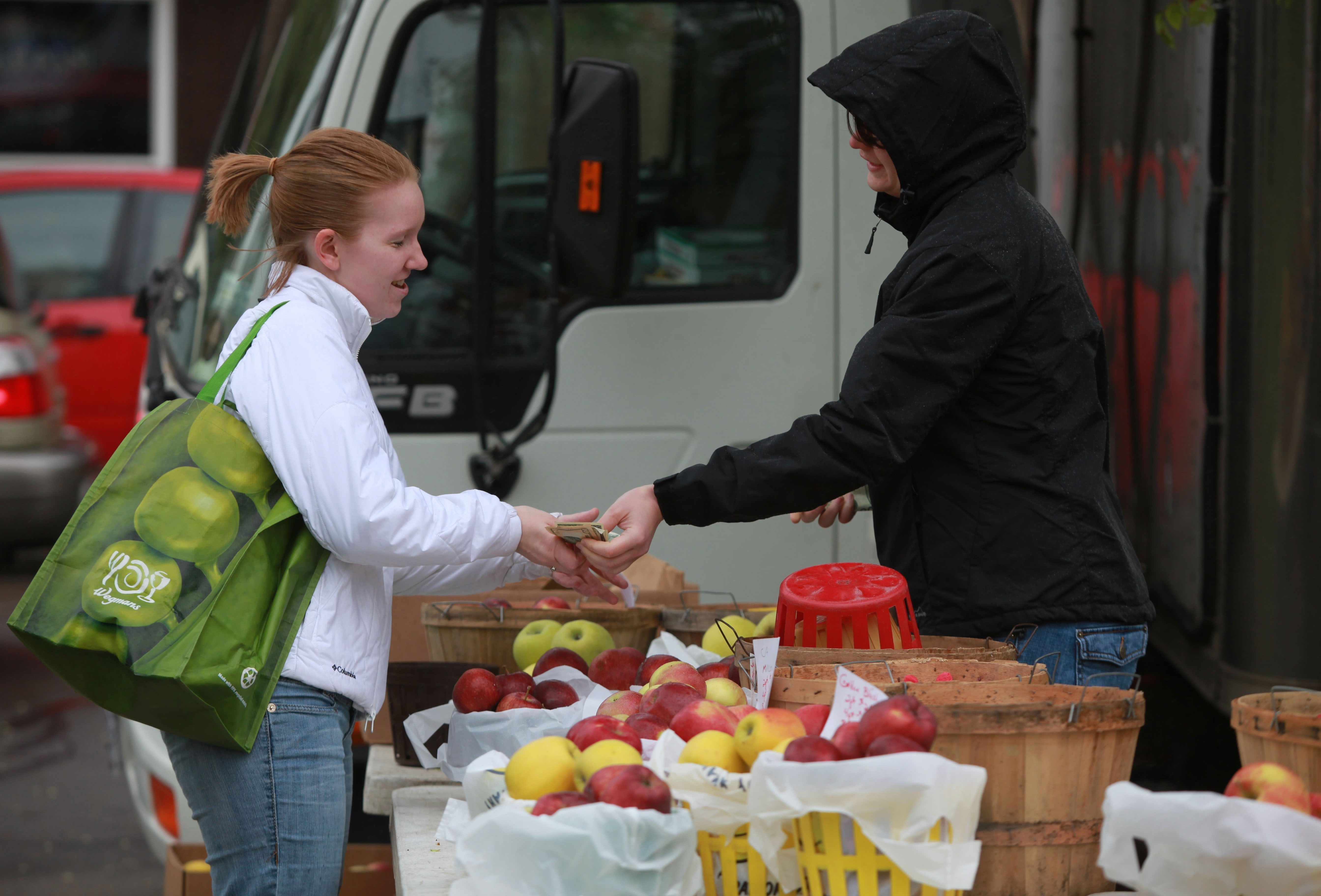 Kristen Muth, left, of Buffalo, buys apples at Dan Tower Farm's stand at the Elmwood-Bidwell Farmers Market, which will close out its season after today and next Saturday. The market is open from 8 a.m. to 1 p.m. on the Elmwood Avenue strip.