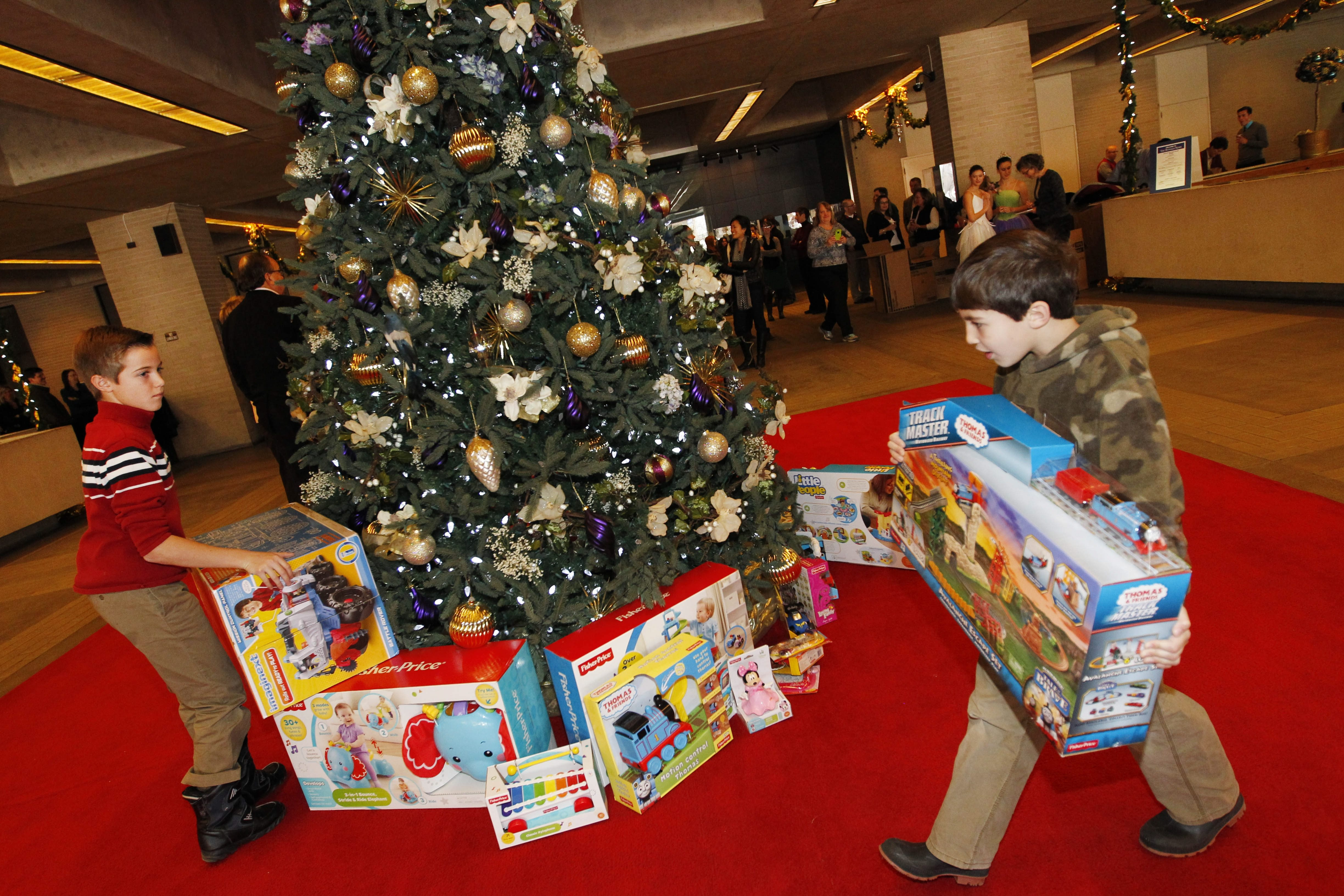 Brothers Paul Mitri, 1, left and Braden Mitri, 7, help to put gifts under the tree during the News Neediest Fund campaign kick-off Friday in the Buffalo News lobby.