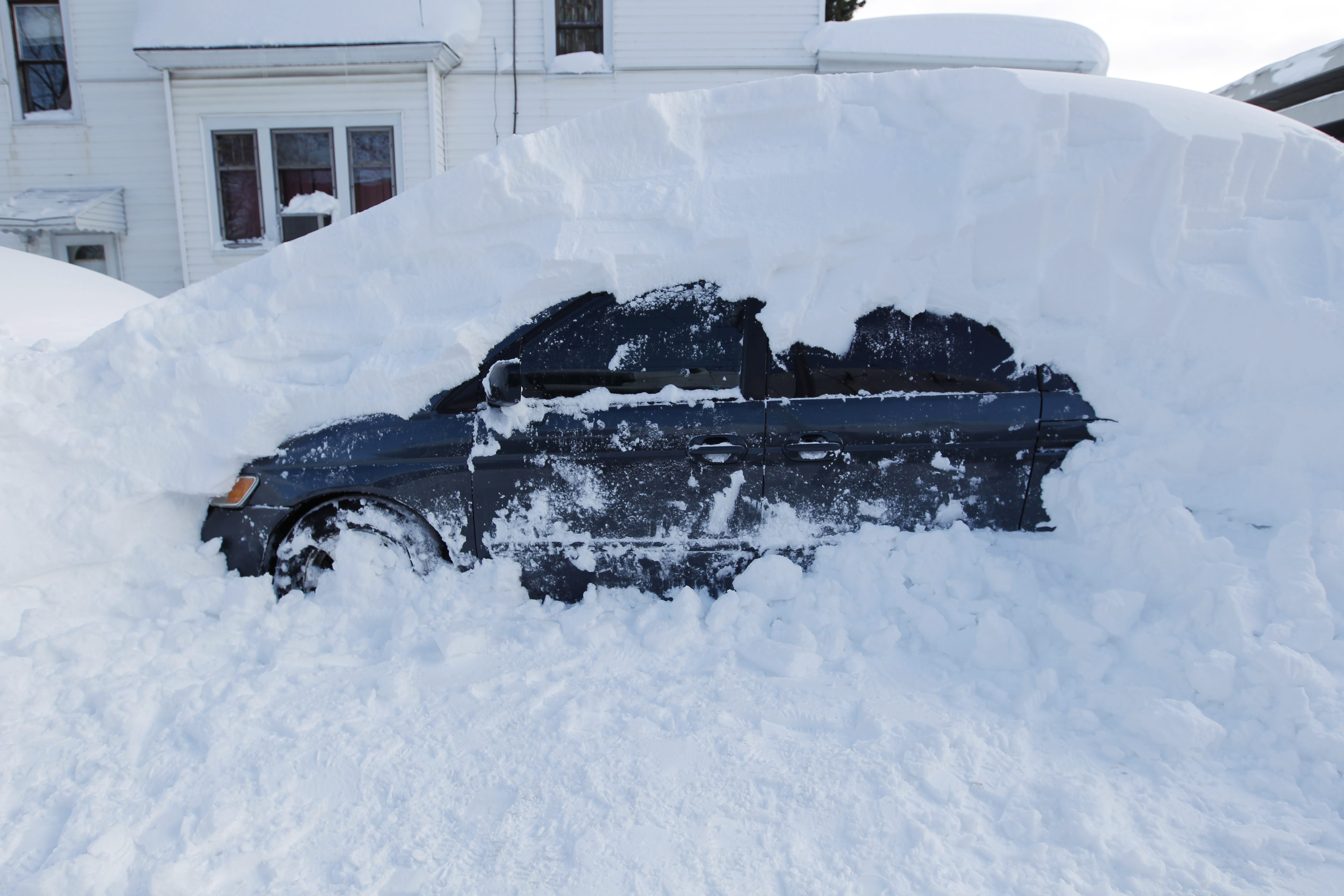 Quickly accumulating lake-effect snow left dozens cars, like this one on Meriden Street in South Buffalo, buried this week. In at least two cases, drivers lost their lives inside cars buried by the relentless waves of snow.
