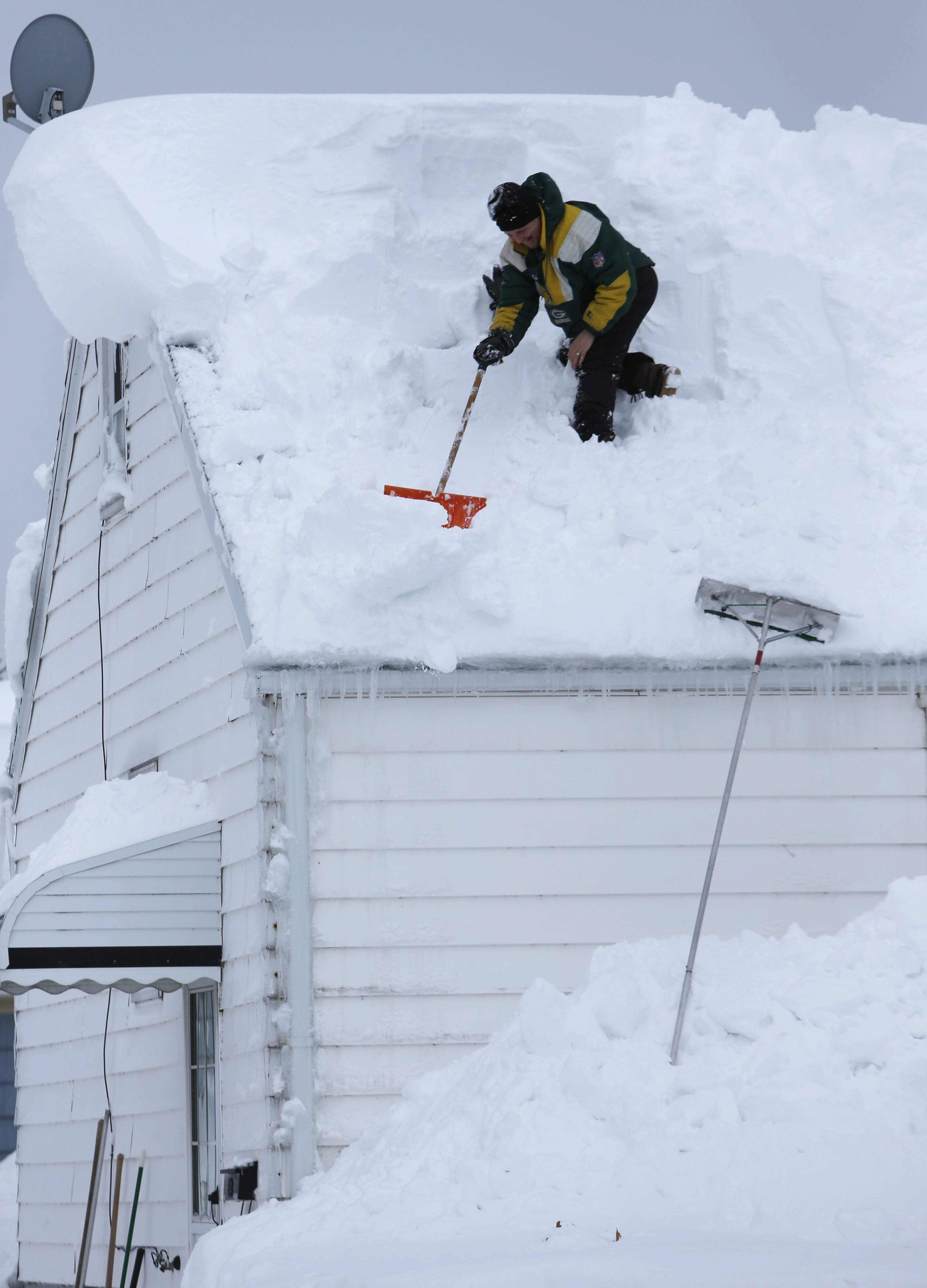 Terry Allen shovels snow off the roof of his home on North Avenue in West Seneca on Thursday.