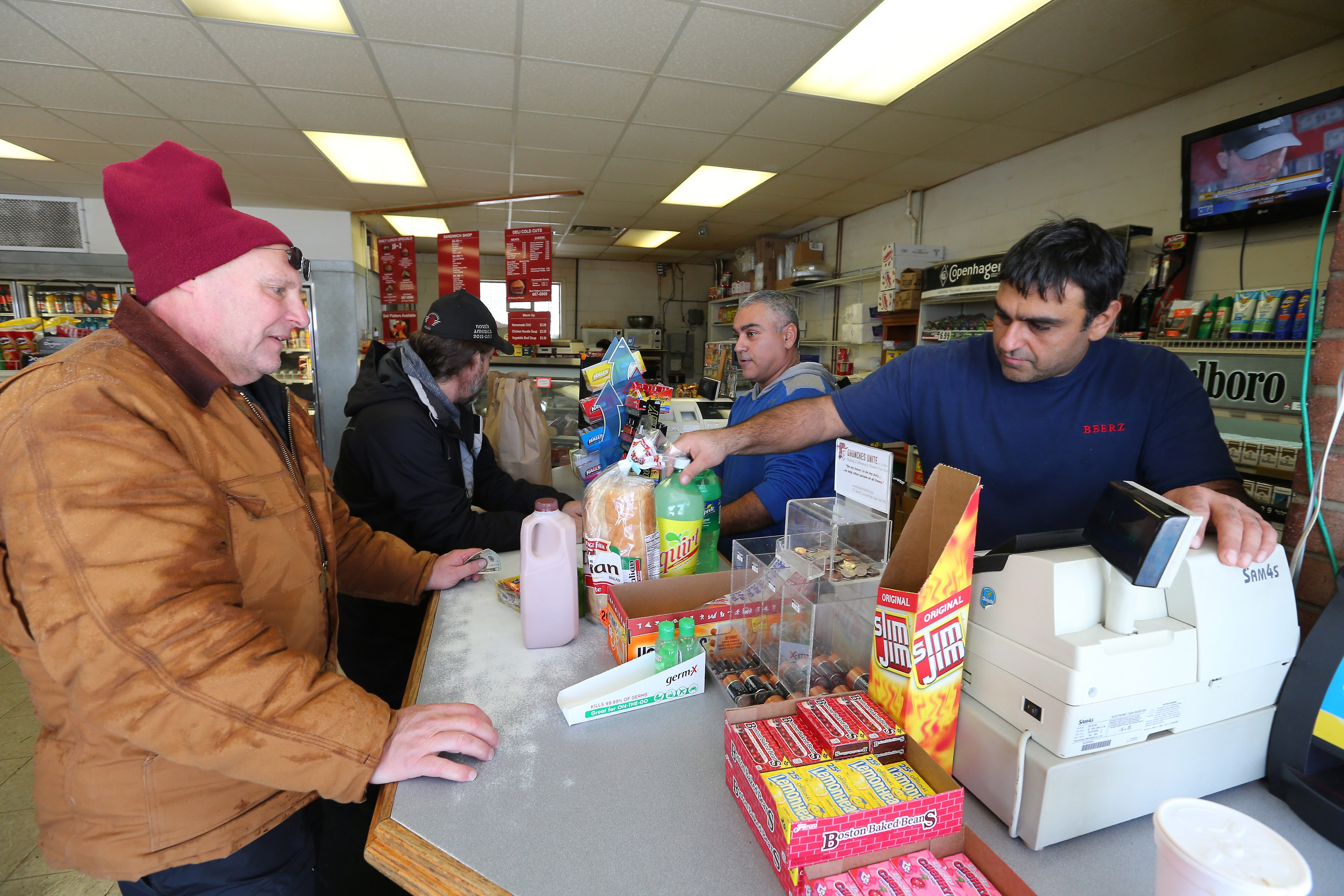 Dan Khangi, right, and his brother George, left, wait on customers at Beerz in Orchard Park Friday. Things are starting to return to normal at area grocery stores and markets as warehouses have reopened and delivery trucks have resumed running.