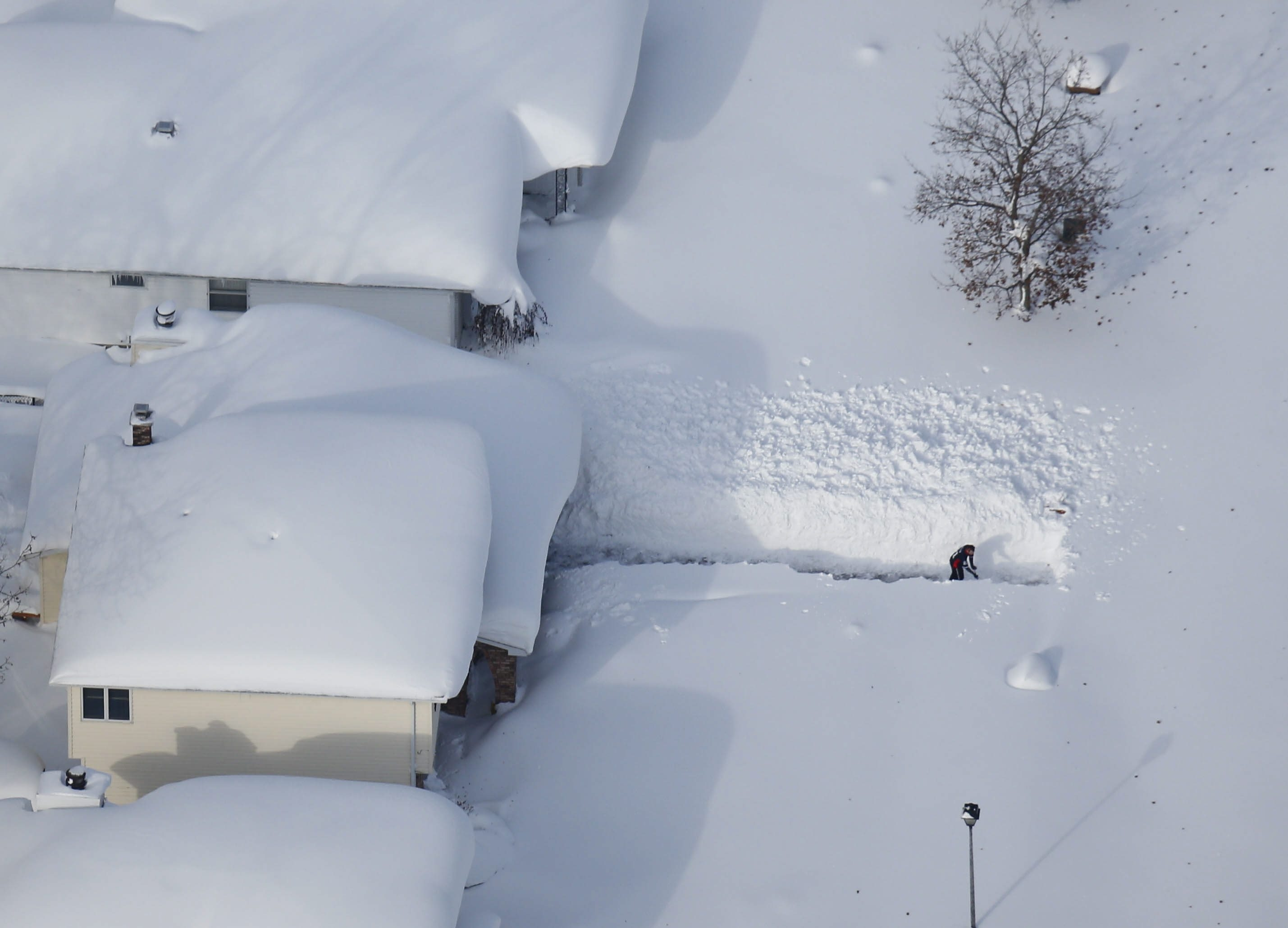 A resident of Depew clears a narrow path from his snow-engulfed house to his unplowed street during the brief calm between two lake-effect storms Wednesday.