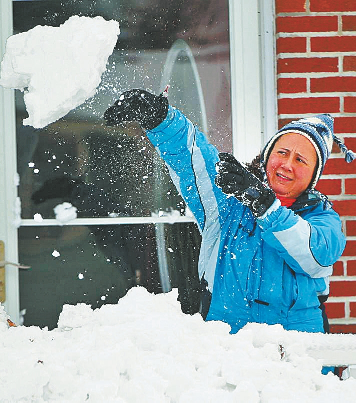 Facing a forecast of more snow, Ann-marie Gaul clears the entrance of her Orchard Park home Wednesday.