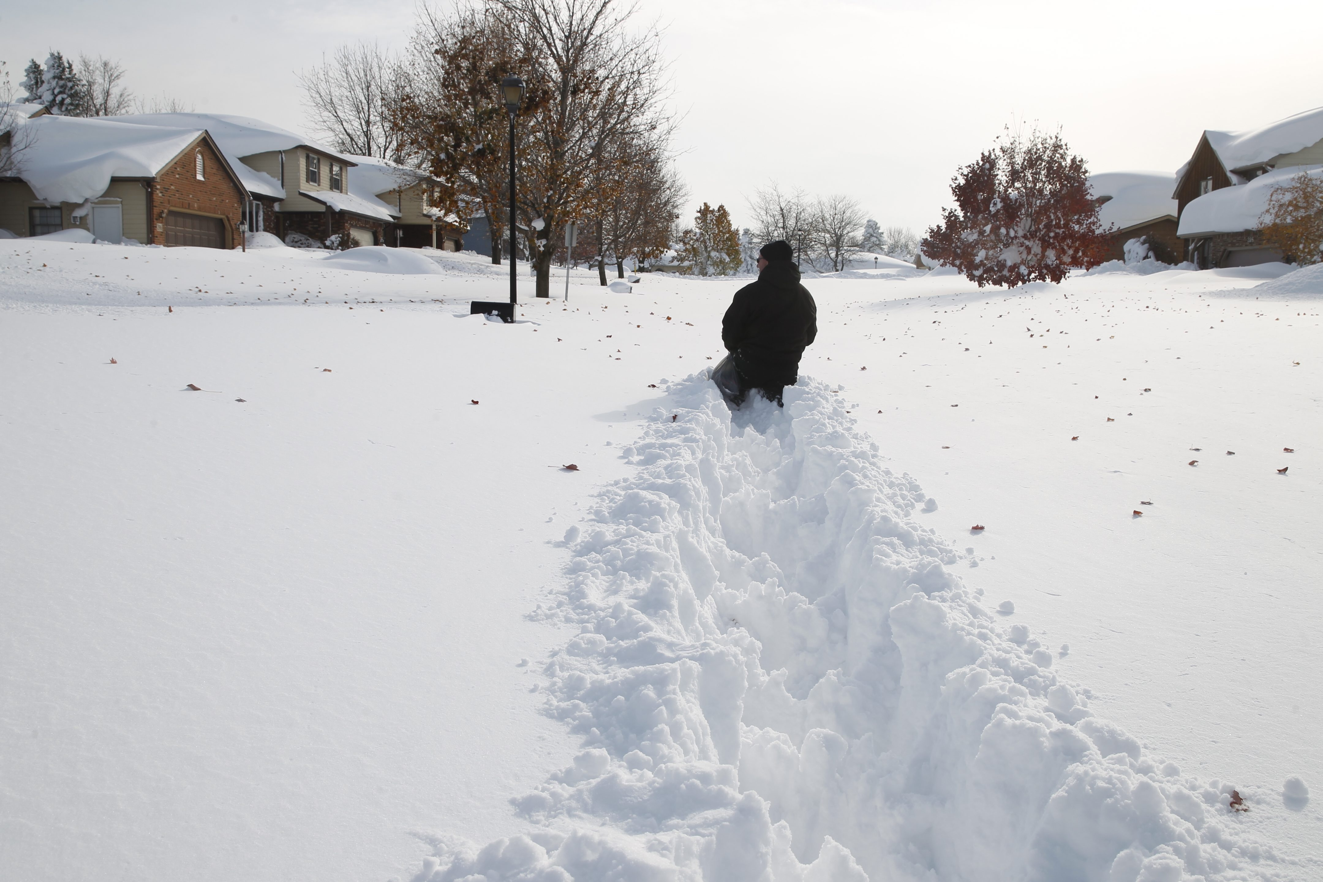 Mike Lackie trudges through hip-deep snow on Barbados Drive in Cheektowaga Wednesday. The neighborhood was among those hardest hit on Tuesday.
