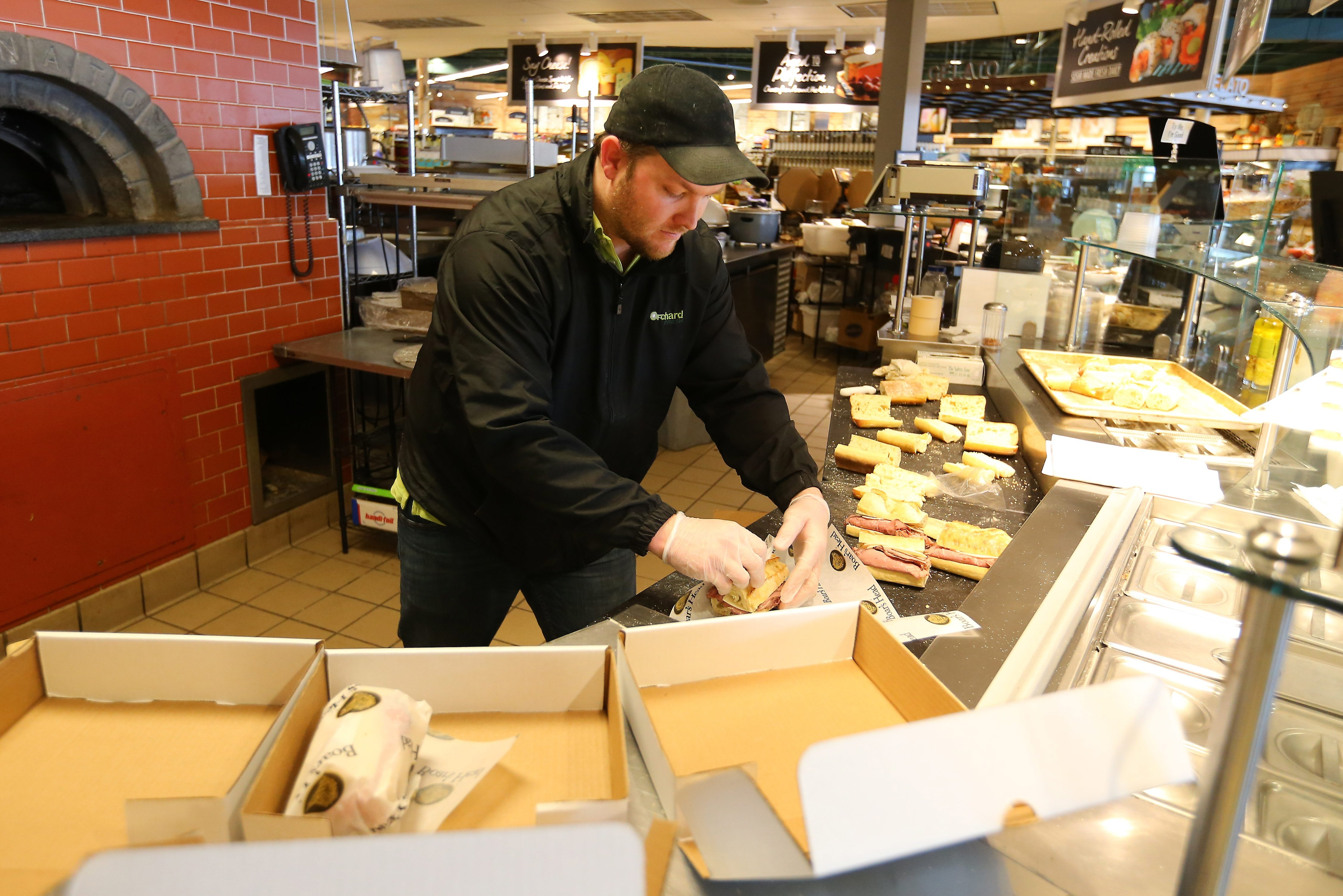 Orchard Fresh store director Kevin Donovan, working more than 48 hours straight, makes sandwiches for staff at the Mercy Ambulatory Care Center in Orchard Park.