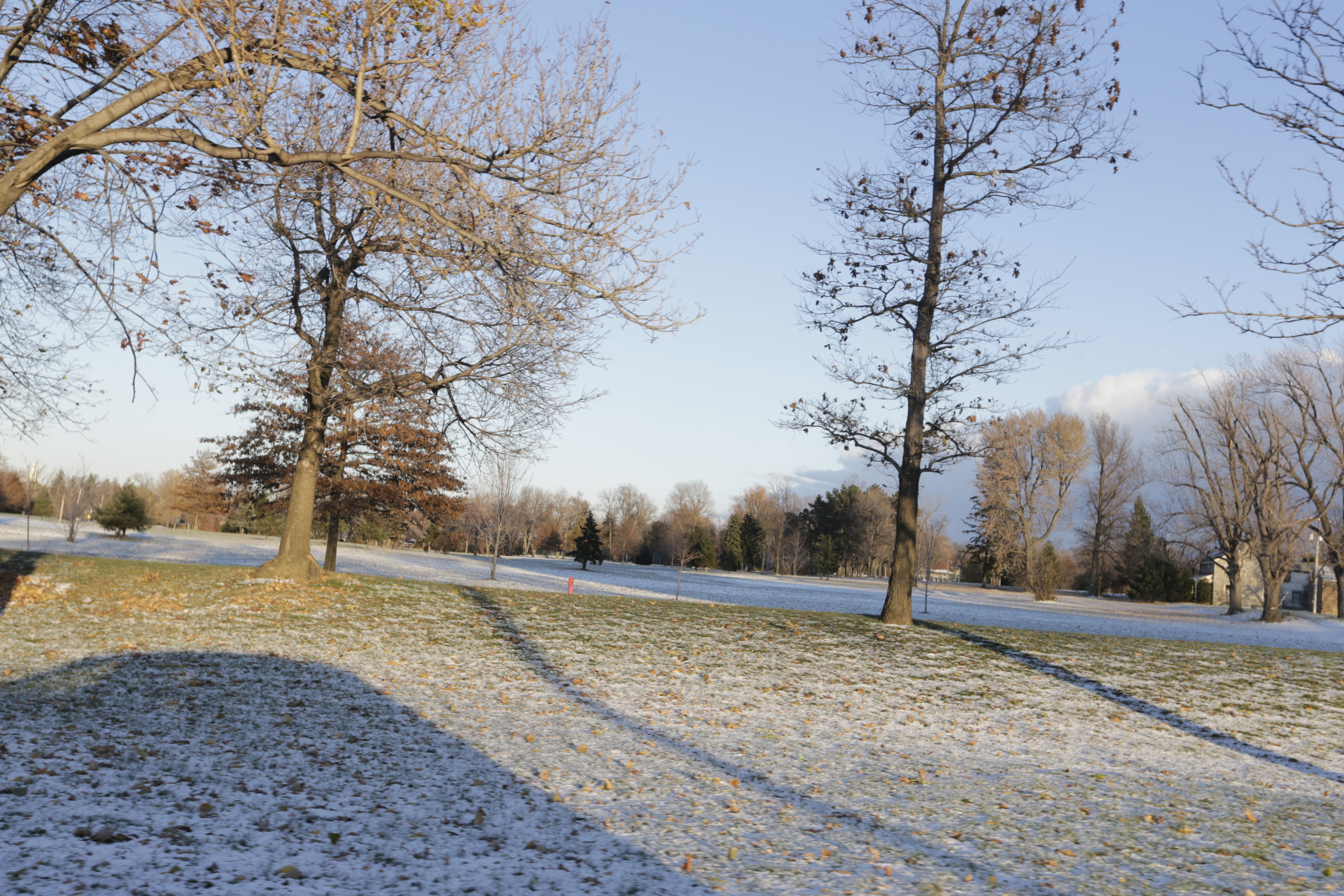 The sun shines in a clear sky and grass pokes through the snow at Grover Cleveland Golf Course in Buffalo on Tuesday, while a lake-effect storm raged a few miles away.