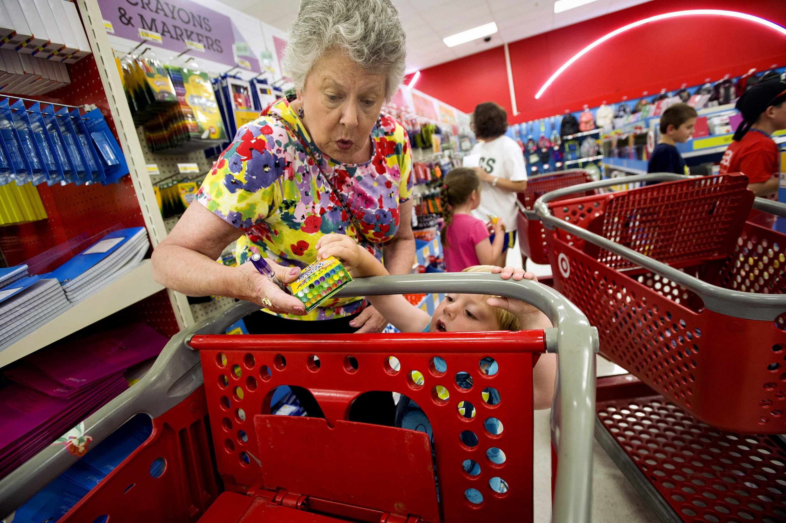 Julie Wilkins helps her grandson, Griffin Brady, 3, put a box of crayons in a shopping cart at a Target store in Memphis, Tenn. Target's third-quarter profits rose, in part, on solid sales of back-to-school items.