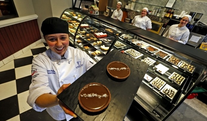 Kara Weber, a staff pastry chef, shows off some of the popular Salted Caramel Tarts in La Patisserie pastry cafe in the Niagara Falls Culinary Institute on Old Falls Street in Niagara Falls. In back, from left, are students Krystal Green, Jessica  Faulhaber and staff pastry cook Stephanie Hauser. (Robert Kirkham/Buffalo News)