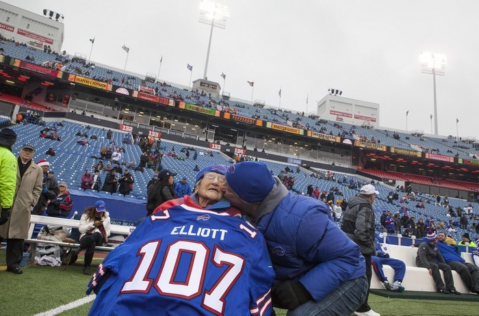 Jim Kelly presents a Buffalo Bills jersey bearing her age on it to Evelyn Elliott, 107, at Ralph Wilson Stadium in Orchard Park before the Dec. 14 game against the Oakland Raiders. Elliott first began watching the team when Kelly was quarterback and the Bills were heading to the playoffs. (New York Times)