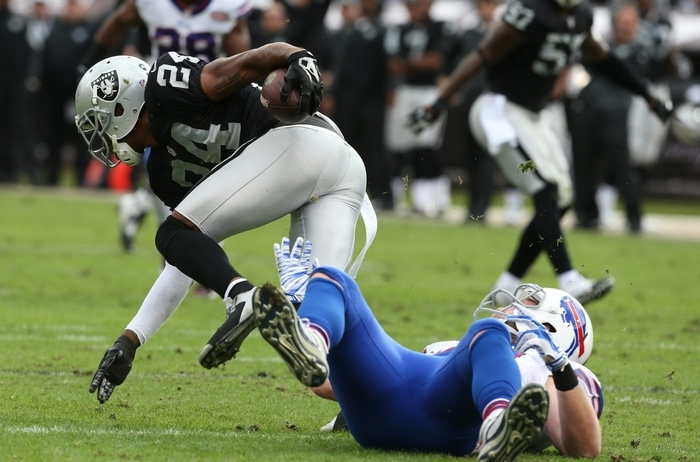 Raiders free safety Charles Woodson intercepts a pass intended for Bills tight end Scott Chandler in the first quarter. (James P. McCoy/Buffalo News)