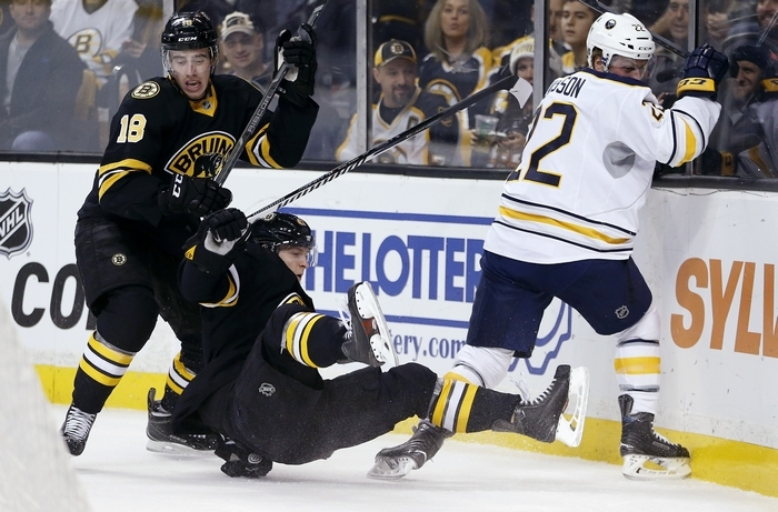 Bruins' Reilly Smith (18) and Torey Krug, center, and Sabres Johan Larsson (22) battle along the boards during Sunday's game in Boston. (Associated Press)
