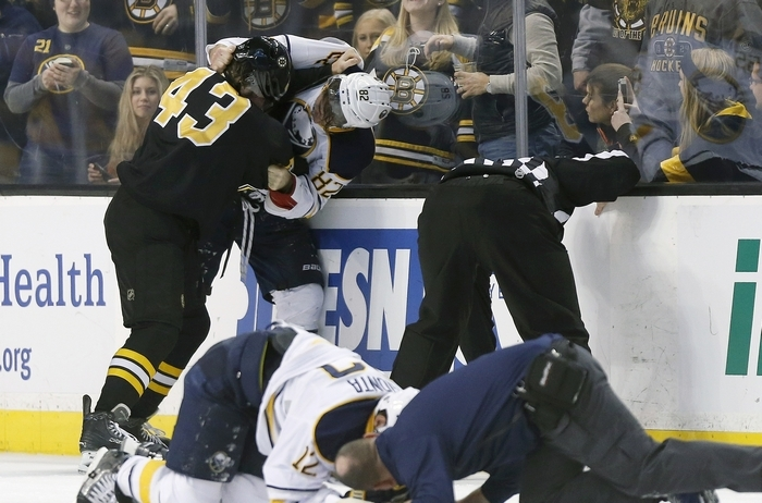 Sabres Brian Gionta is being attended while teammate Marcus Foligno tangles with the guilty party Bruins' Matt Bartkowski during Sunday's game in Boston. (Associated Press)