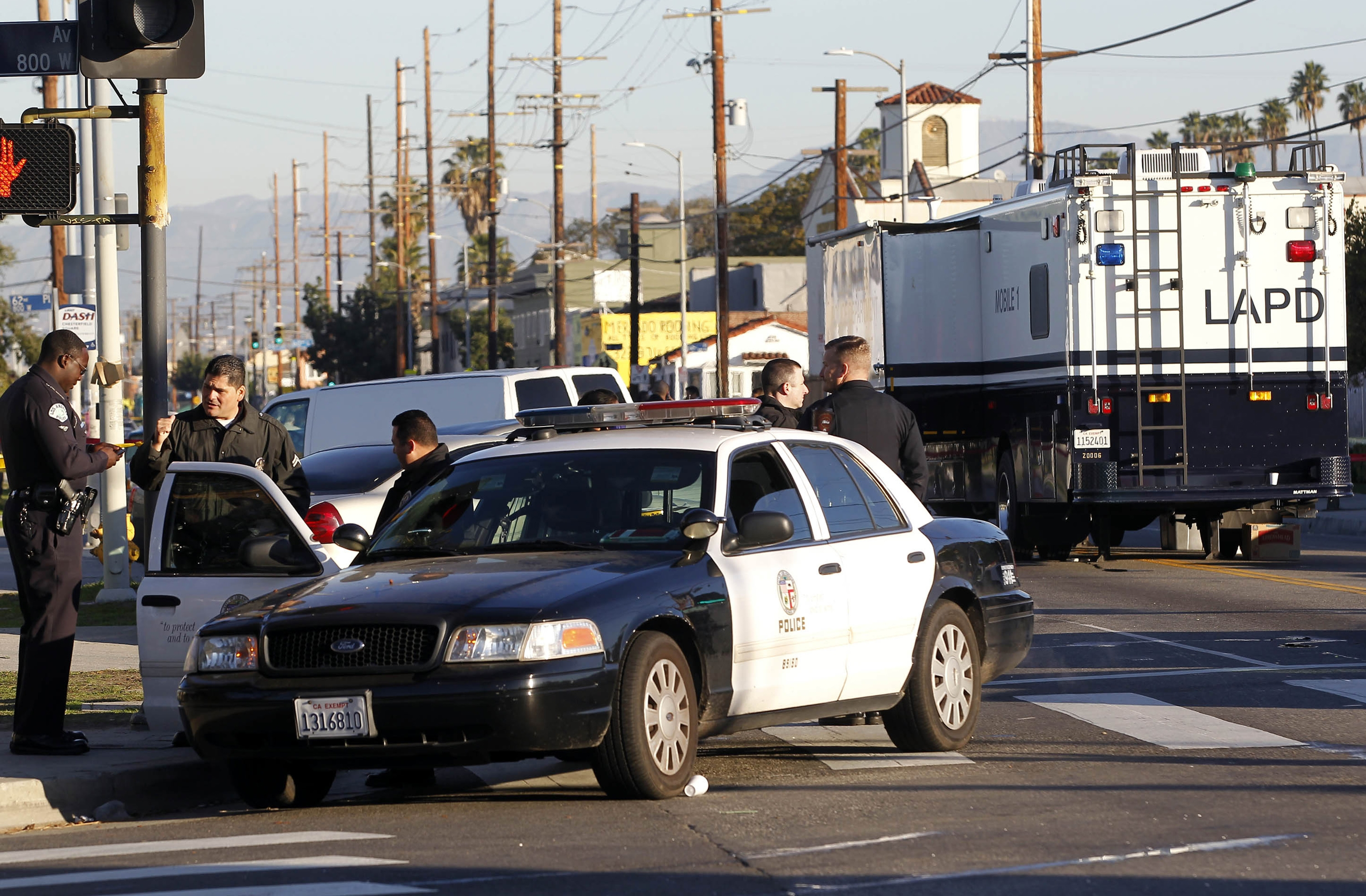 Los Angeles police officers investigate a shooting in South Central Los Angles on Monday. A man fired a rifle at two Los Angeles officers in a patrol car on Sunday night but no one was injured in the attack that comes amid tension nationwide between police and protesters rallying against their tactics.