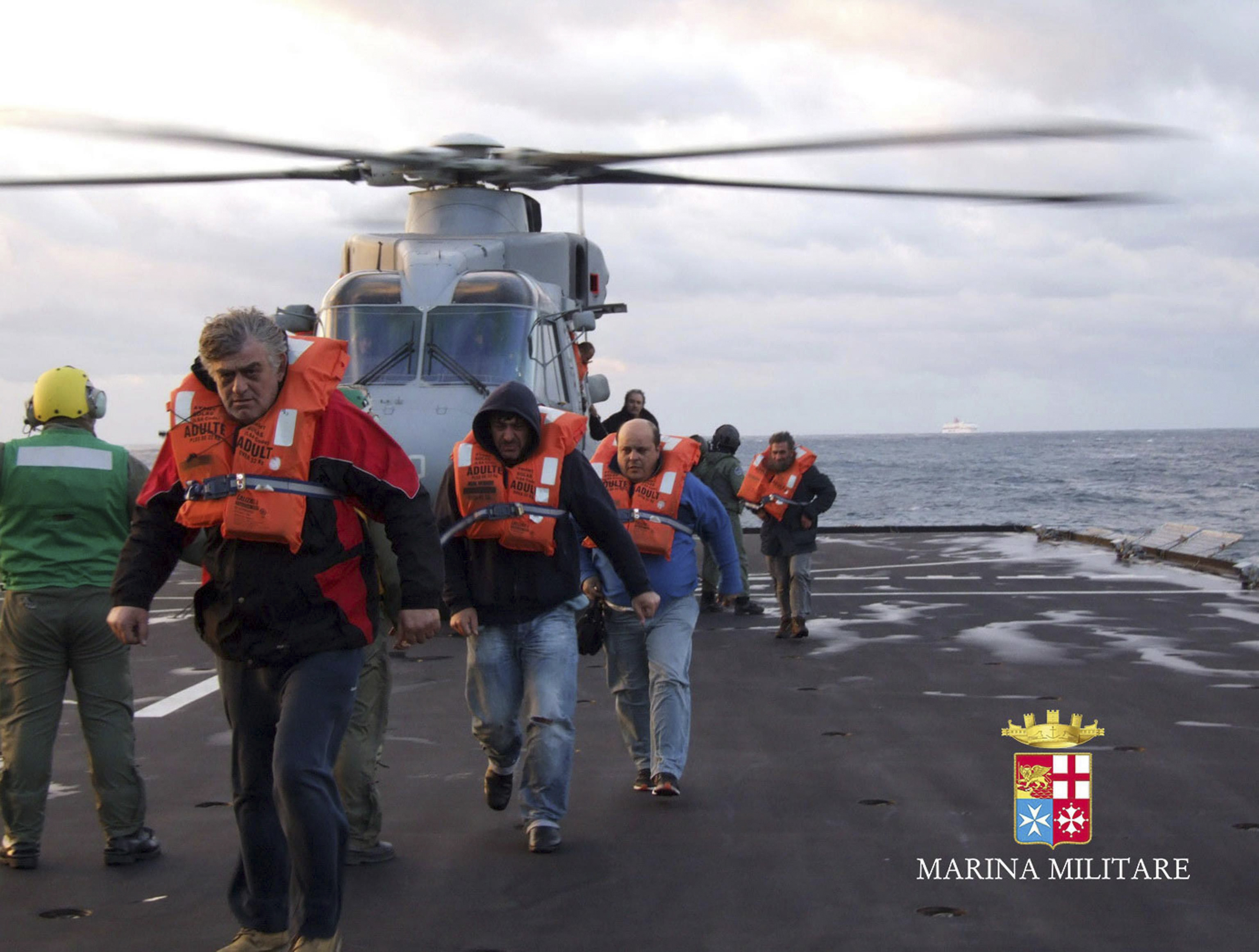 Passengers rescued from the Norman Atlantic ferry land on board the Italian Navy ship San Giorgio.