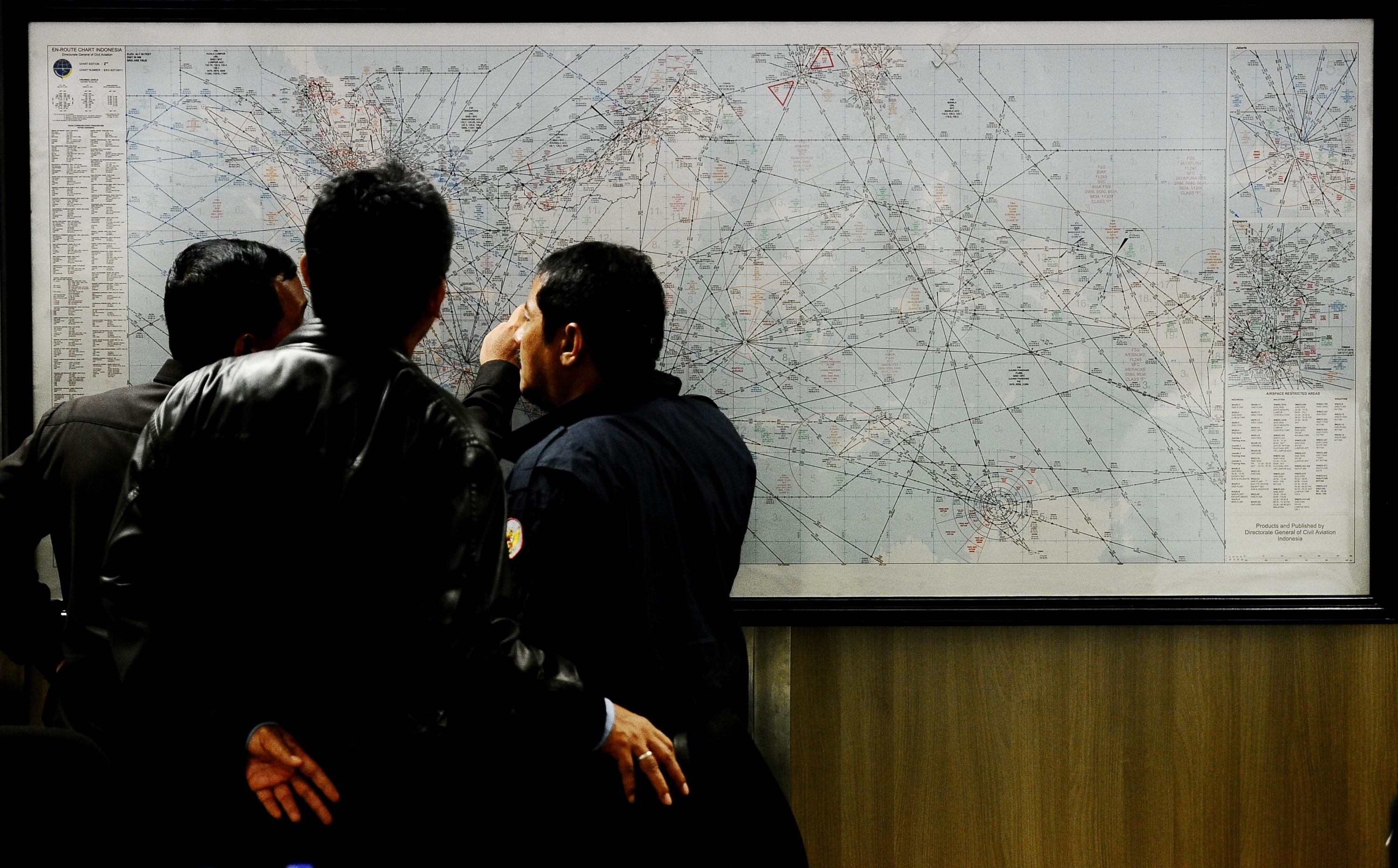 Indonesia Search and Rescue officers inspect the operational air navigation map during the investigation of missing AirAsia Flight QZ8501 at the crisis centre of Juanda International Airport Surabaya on Sunday.