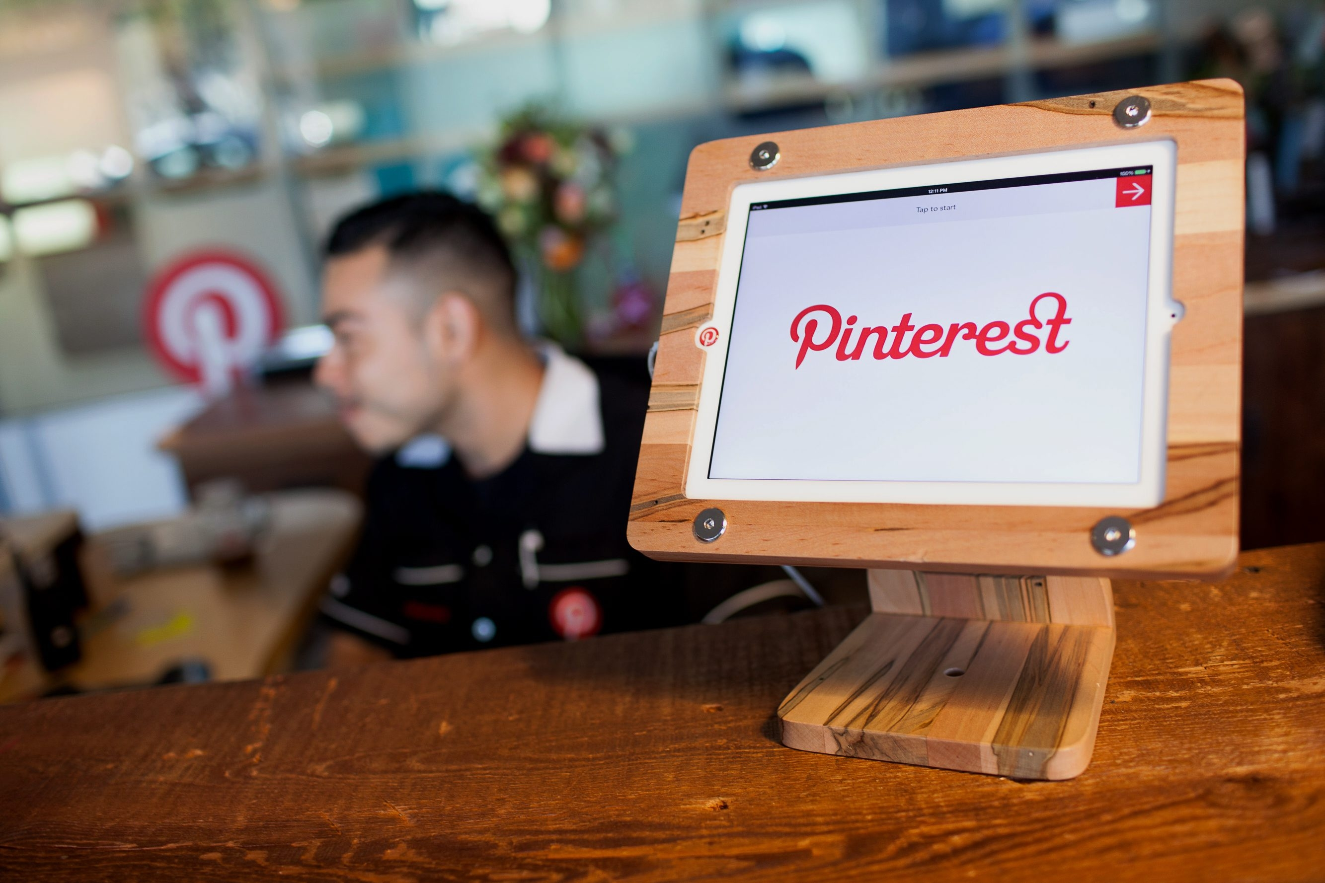 Pinterest Inc. signage is seen on an Apple iPad at the reception desk of the company's headquarters in San Francisco in November. Pinterest, which wants to compete for ad dollars with the likes of Google, Twitter and Facebook, plans to start selling ads on the site to any marketer on New Year's Day.