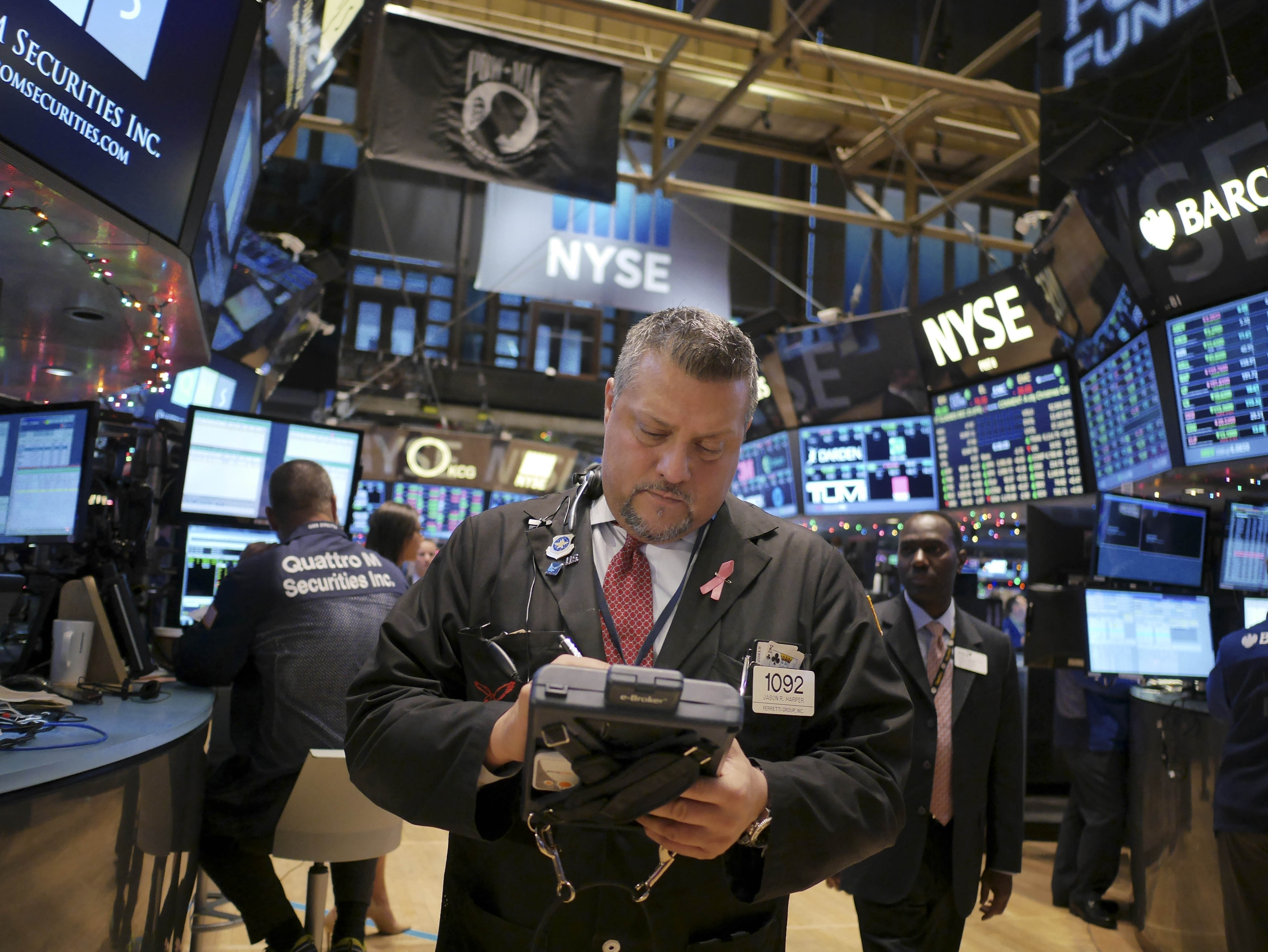 Traders work on the floor at the New York Stock Exchange. The Russell 2000 Index climbed to an all-time high Friday and the Nasdaq Composite Index reached a level unseen since 2000.